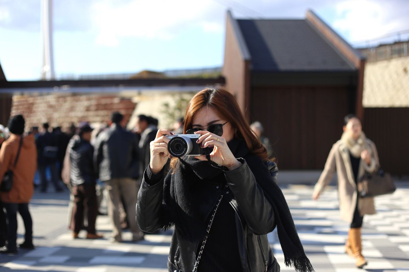 Taking a photo Photography Themes Photographing Camera - Photographic Equipment Real People Lifestyles Leisure Activity Standing Outdoors Women Day Portrait Built Structure Sky Men Young Adult Young Women Technology Architecture Photographer One Person