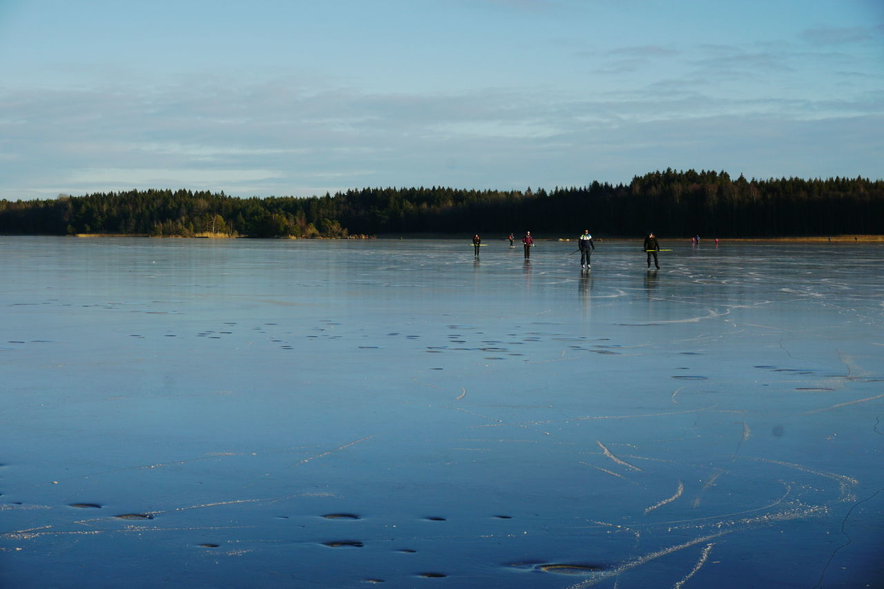 People Ice-Skating On Frozen Lake Against Sky