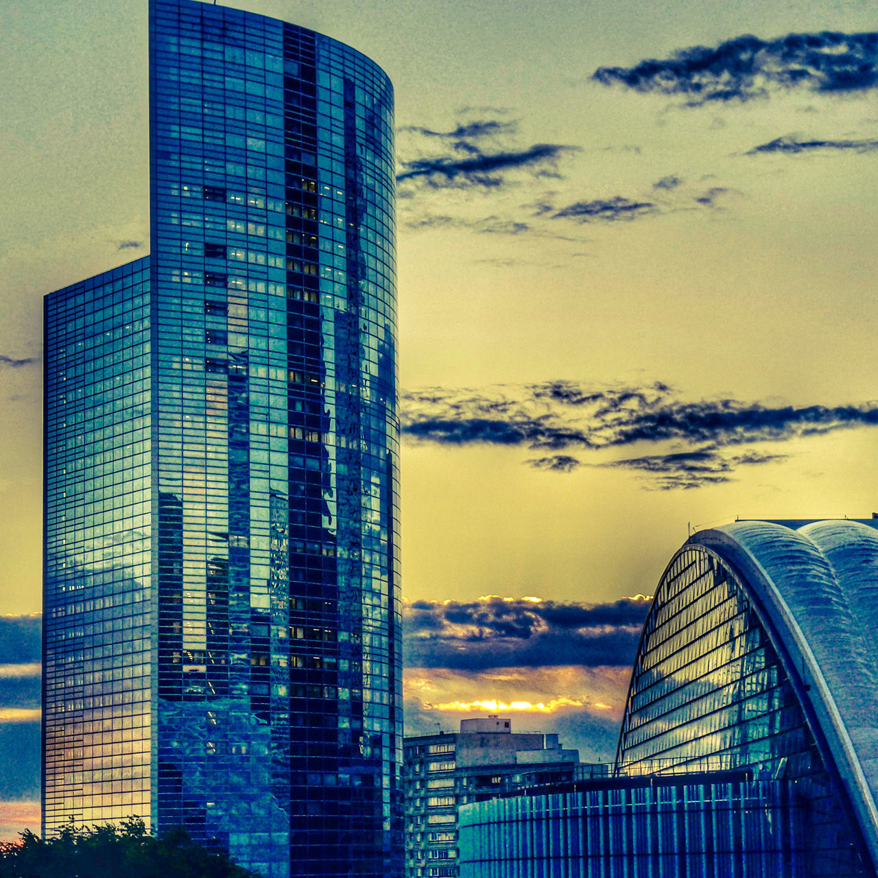 architecture, built structure, building exterior, skyscraper, modern, sky, city, tower, no people, sunset, outdoors, low angle view, day, cloud - sky, travel destinations, tall, cityscape