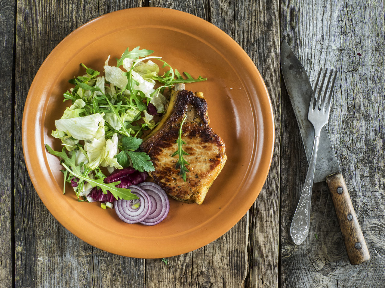 Roasted pork chop on a plate with a green salad, red onion on an old wooden weathered table Arugula Chop Food Food And Drink Freshness Garnish Green Meal No People Old Onion Plate Pork Ready-to-eat Relaxing Roast Chicken Roasted Salad Spice Table Weathered Wood - Material Wooden