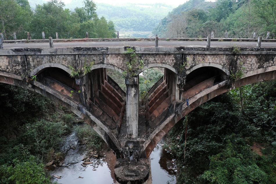 QUANG TRI, VIET NAM- FEB 23, 2016: Dau Mau bridge on Ho Chi Minh trail, an old bridge link with Vietnam war history make by French locate at Cam Lo, with amazing architect, pass green jungle Abstract Achitecture Amazing Ancient ARCHITECT ASIA Bridge Corrupt Dau Mau Dau Mau Bridge Forest Green Historical History Ho Chi Minh Trail Jungle Lanscape Old Quang Tri River Scene Viet Nam Vietnam Vietnam War Vietnamese