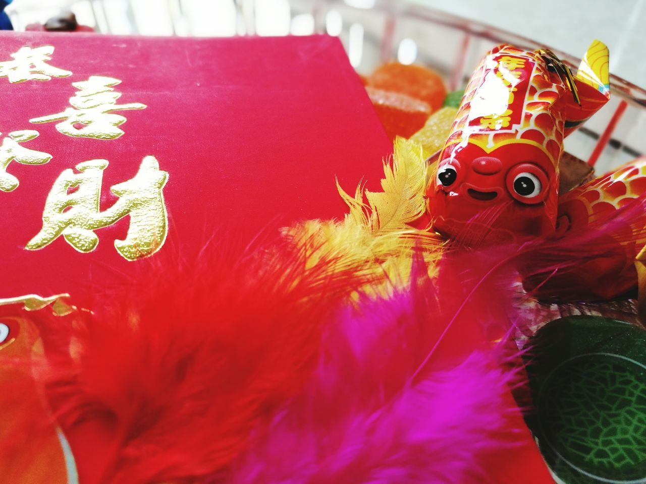 Red Animal Representation Chinese New Year Celebration Cultures Tradition No People Close-up Indoors  Colored Feathers Lunar New Year Red Packet Sweets Feathers♡ Candies! Gold Lettering Setting The Table Fish Full Frame