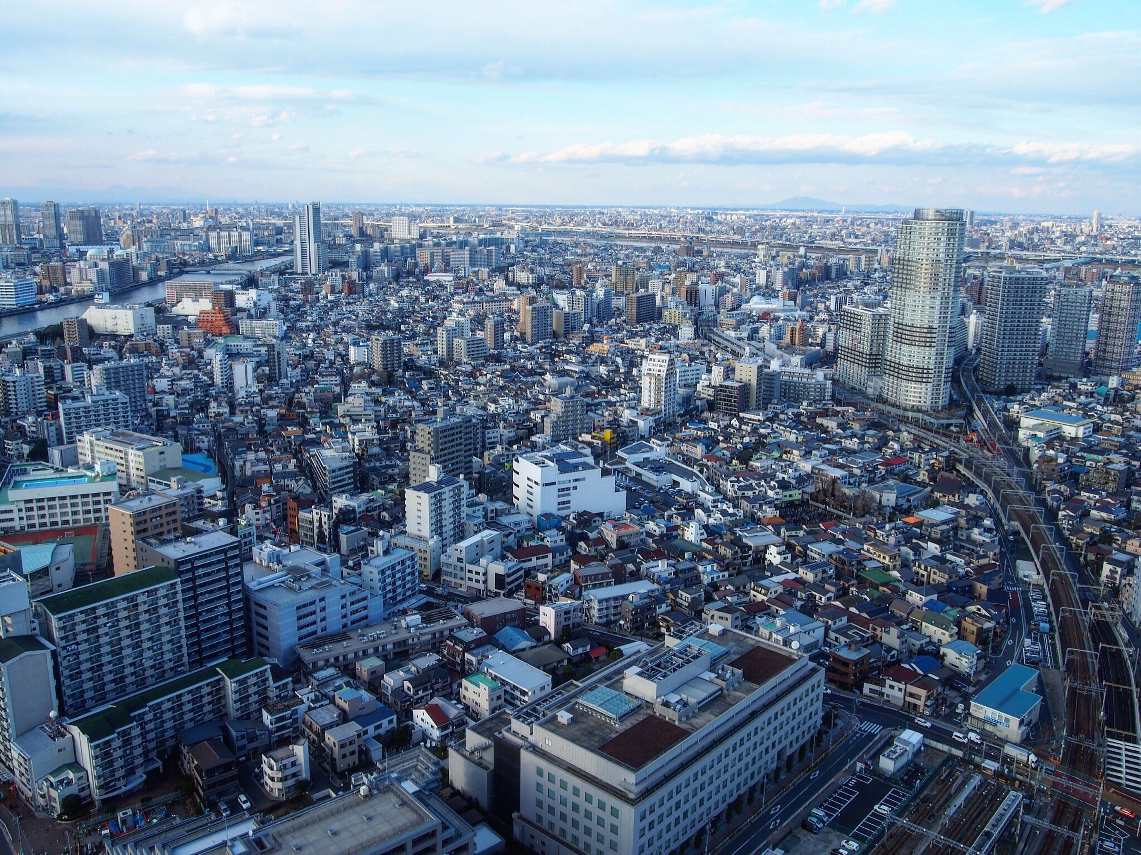 cityscape, city, building exterior, architecture, built structure, crowded, high angle view, skyscraper, residential district, tower, aerial view, sky, city life, capital cities, tall - high, modern, residential building, office building, cloud - sky, residential structure