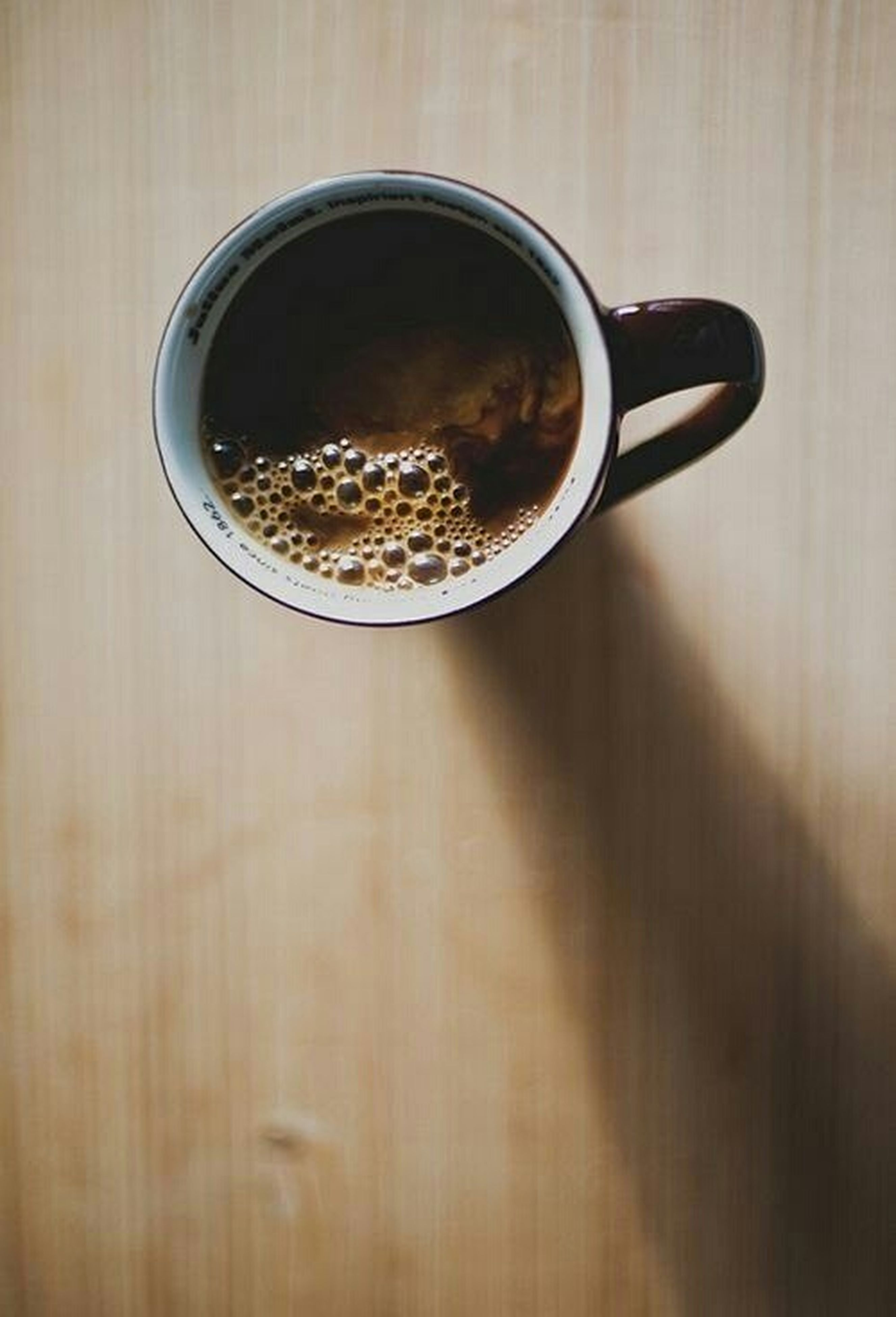 indoors, drink, refreshment, close-up, food and drink, table, coffee cup, freshness, still life, reflection, no people, directly above, cup, circle, wood - material, coffee - drink, selective focus, coffee, glass - material, glass