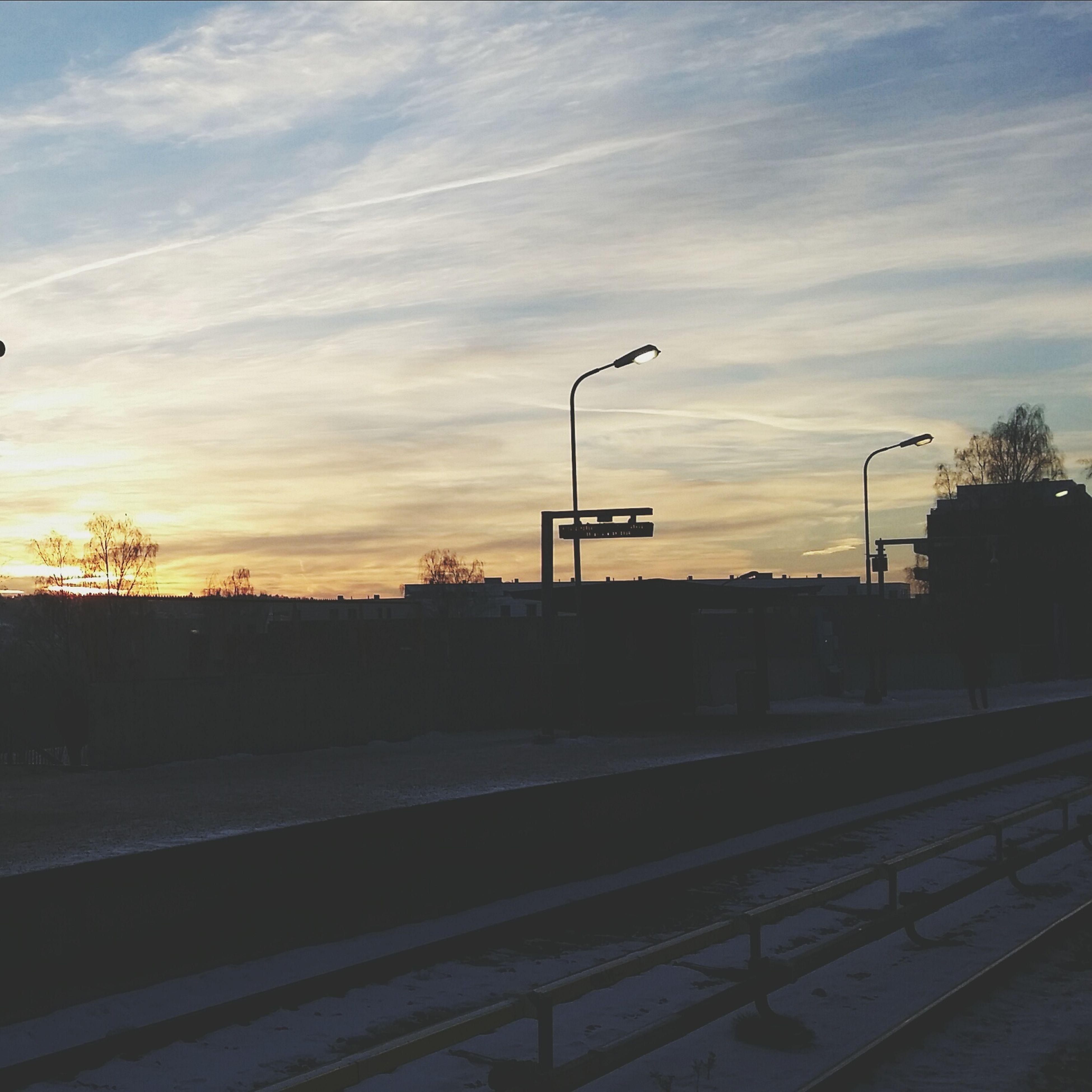 railroad track, sky, sunset, transportation, cloud - sky, street light, rail transportation, silhouette, tree, railing, built structure, road, railroad station, the way forward, railroad station platform, cloud, public transportation, no people, architecture, outdoors