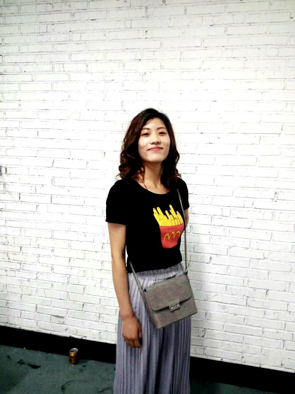 looking at camera, real people, one person, wall - building feature, standing, brick wall, front view, three quarter length, portrait, young adult, mid adult, leisure activity, lifestyles, young women, casual clothing, long hair, smiling, day, happiness, indoors, beautiful woman, people