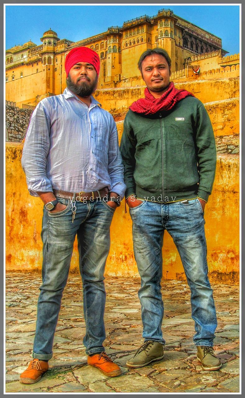 portrait, looking at camera, front view, standing, outdoors, real people, day, togetherness, building exterior, smiling, full length, architecture, lifestyles, men, friendship, adult, young adult, only men, people, adults only