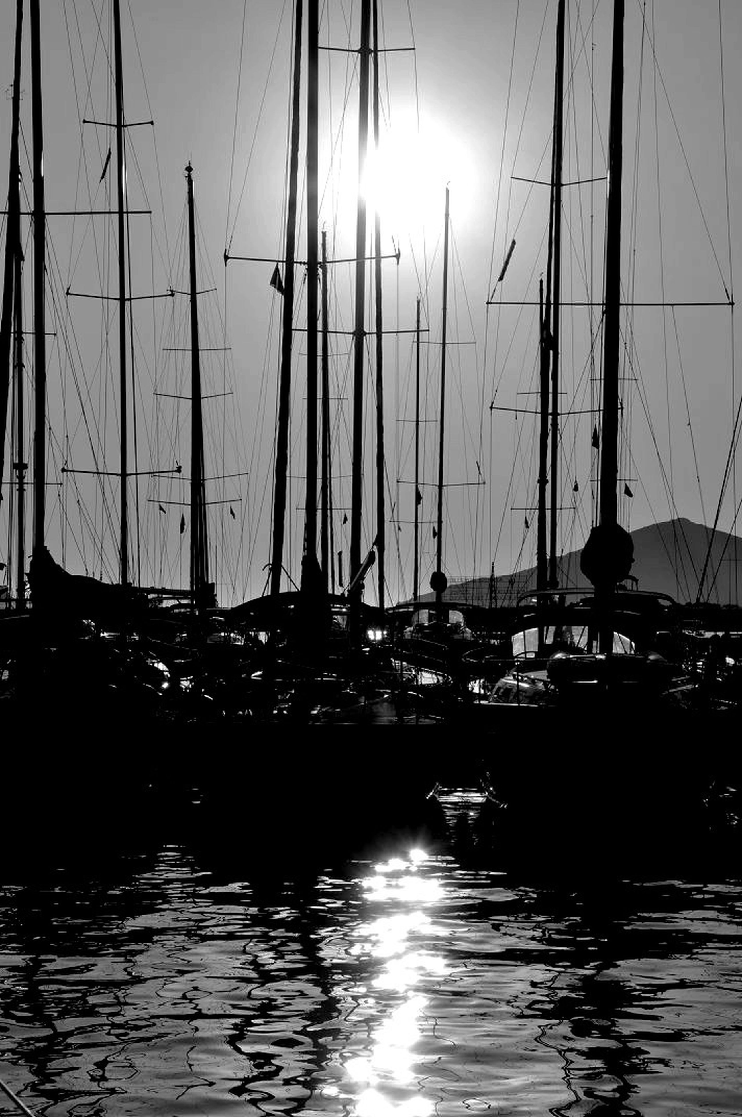 water, waterfront, reflection, transportation, rippled, sun, nautical vessel, sunlight, sunbeam, sea, sunset, sky, river, boat, nature, mode of transport, silhouette, outdoors, mast, built structure