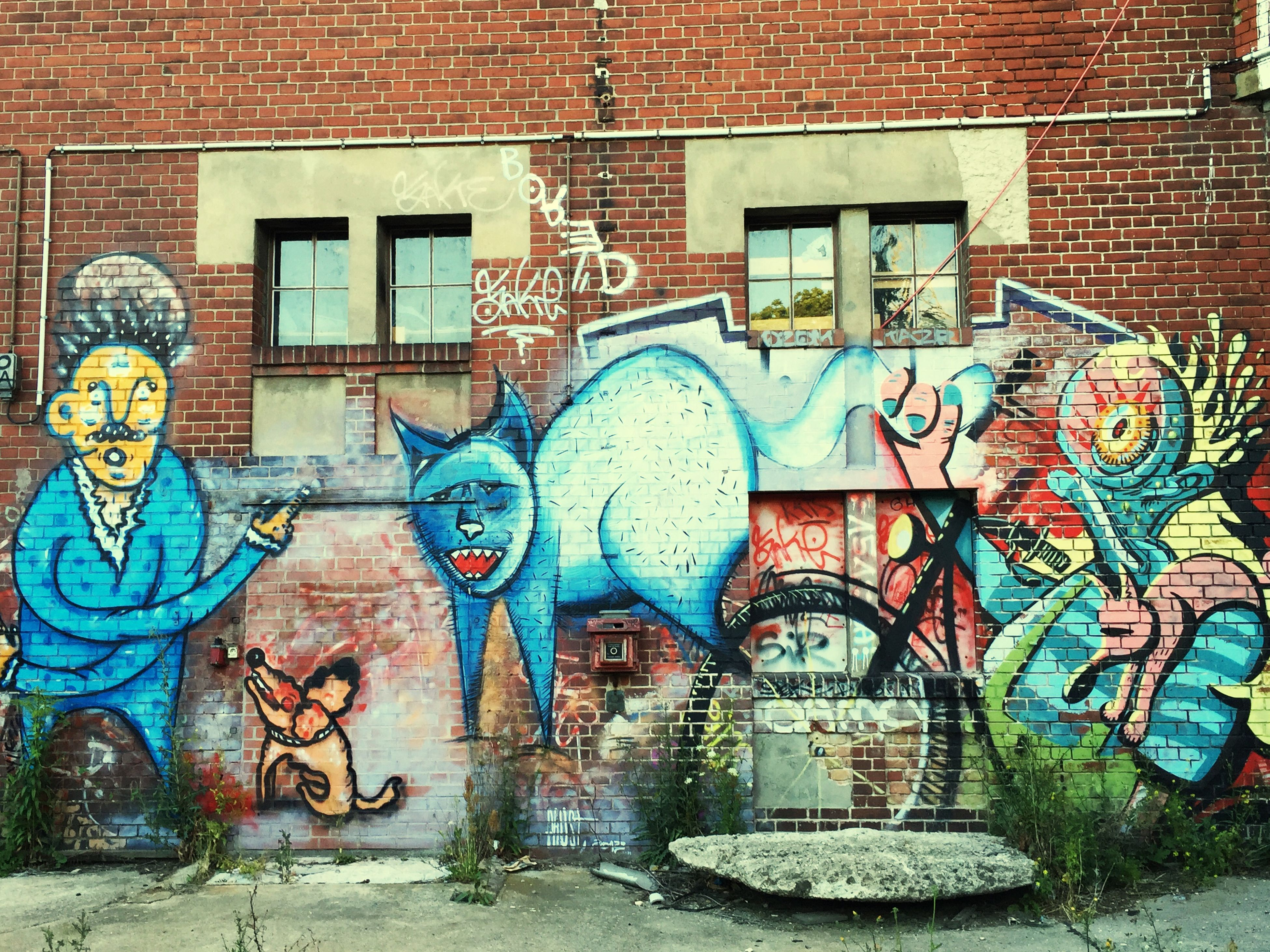 architecture, graffiti, built structure, building exterior, art and craft, art, creativity, wall - building feature, human representation, brick wall, window, multi colored, street art, mural, wall, day, building, street, outdoors