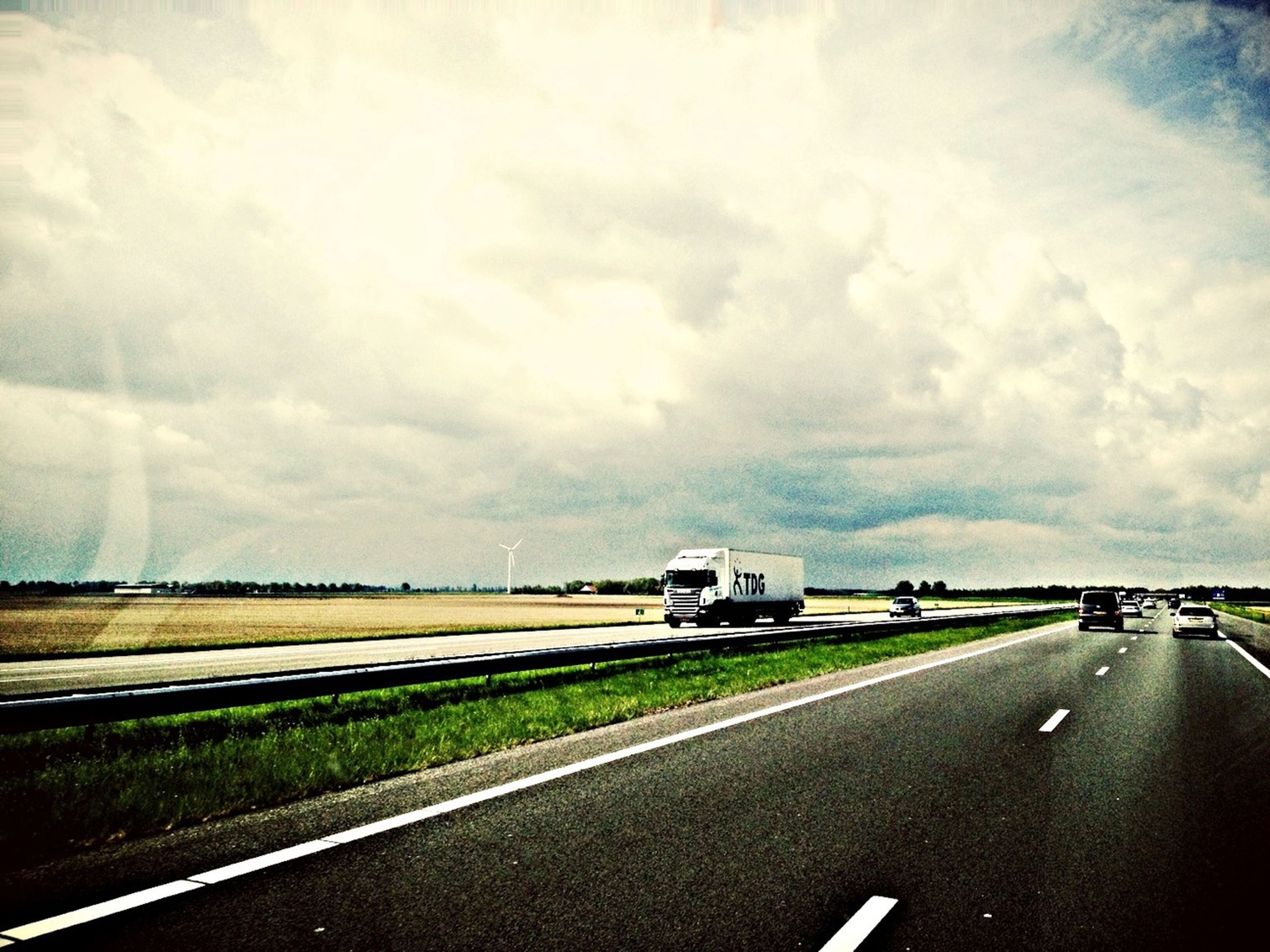 transportation, road, road marking, the way forward, sky, car, land vehicle, cloud - sky, mode of transport, street, diminishing perspective, country road, cloudy, vanishing point, highway, overcast, landscape, cloud, asphalt, empty road