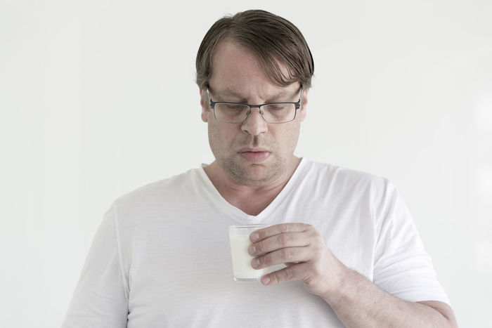 Man with glasses looking down on his glass of milk Adults Only Day Desperate Drink Drinking Drinking Glass Drinking Water Eyewear Food And Drink Front View Glass Glasses Healthy Food Healthy Lifestyle Humor Looking Down Men Milk One Man Only One Person Only Men People Studio Shot Ugly Face White Background
