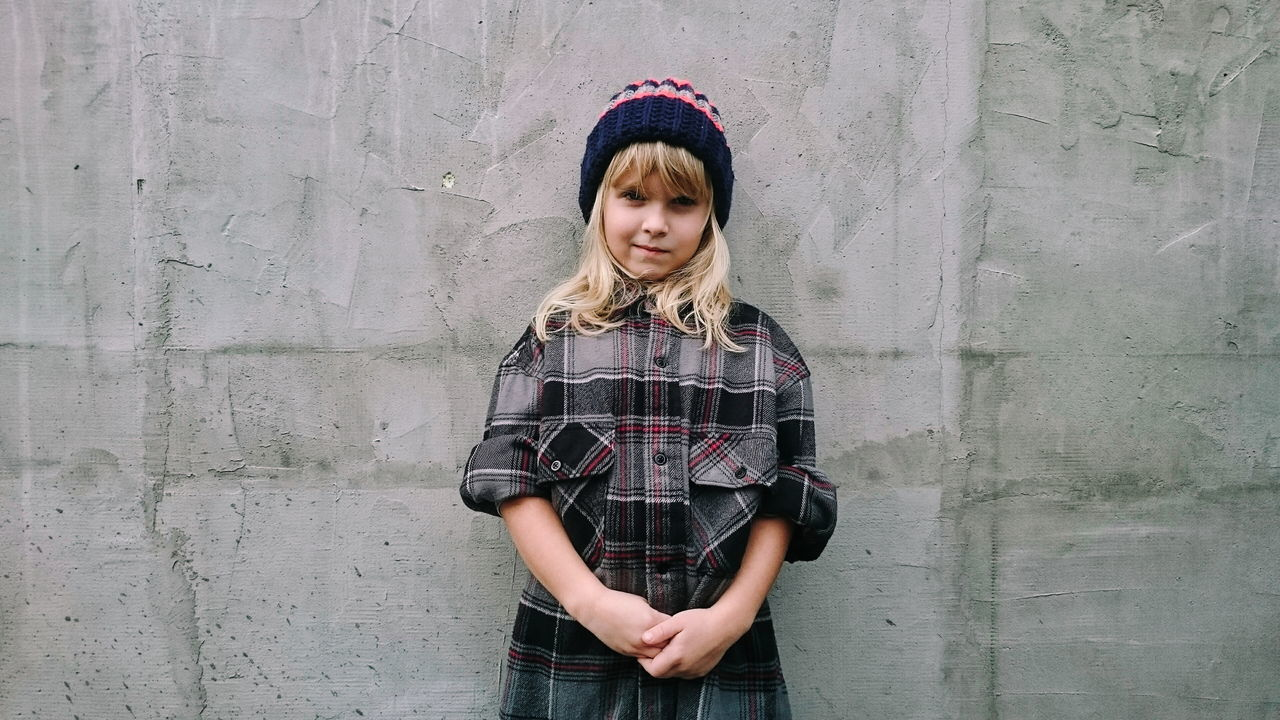Portrait Of Blond Girl Standing Against Concrete Wall
