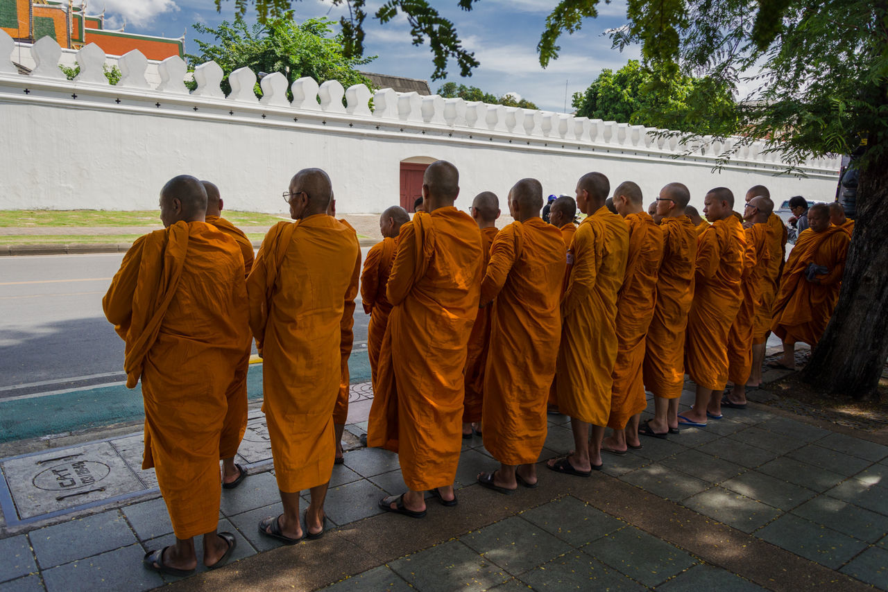 religion, spirituality, large group of people, men, in a row, real people, rear view, architecture, built structure, day, place of worship, travel destinations, building exterior, outdoors, sky, adult, people