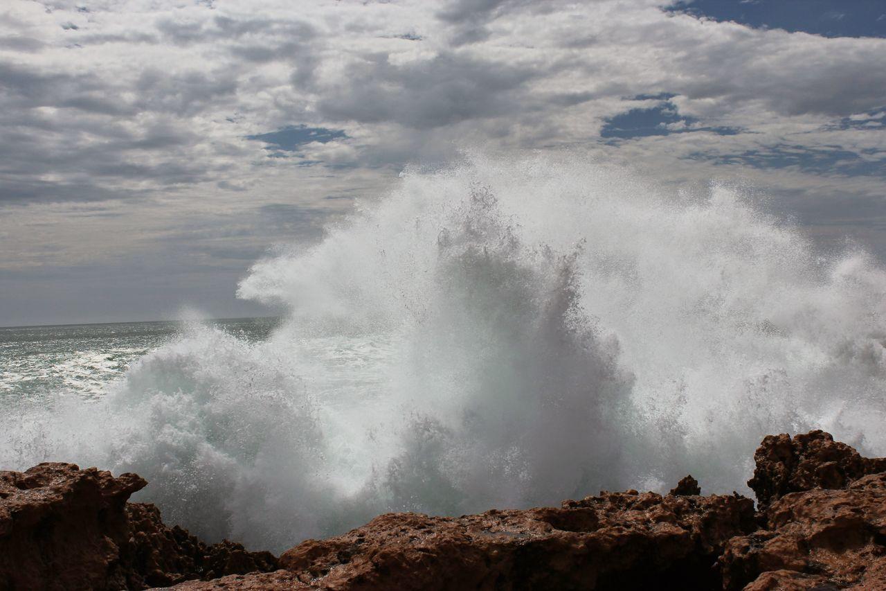 Sea Waves Splashing On Rock Against Clouds
