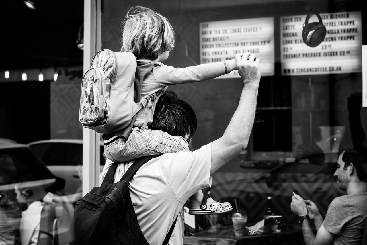 Backgrounds Childhood Day Family Father Father & Son Food Lifestyles Men Outdoors People Piggyback Real People Rear View Restaurant Togetherness Two People Window Let's Go Together