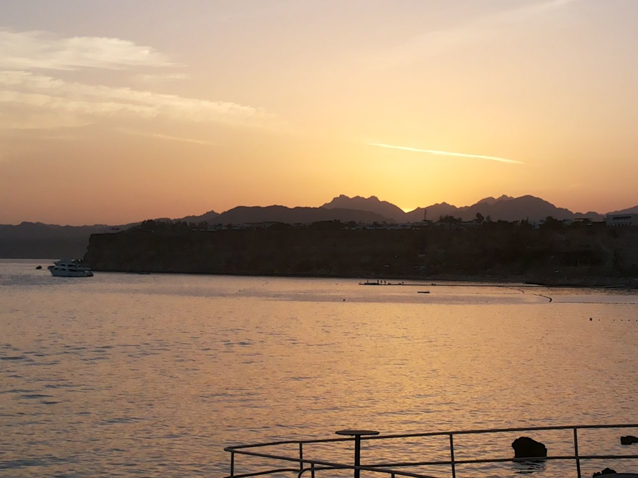 sunset, water, scenics, nature, railing, beauty in nature, sky, sea, tranquility, outdoors, tranquil scene, mountain, no people, day