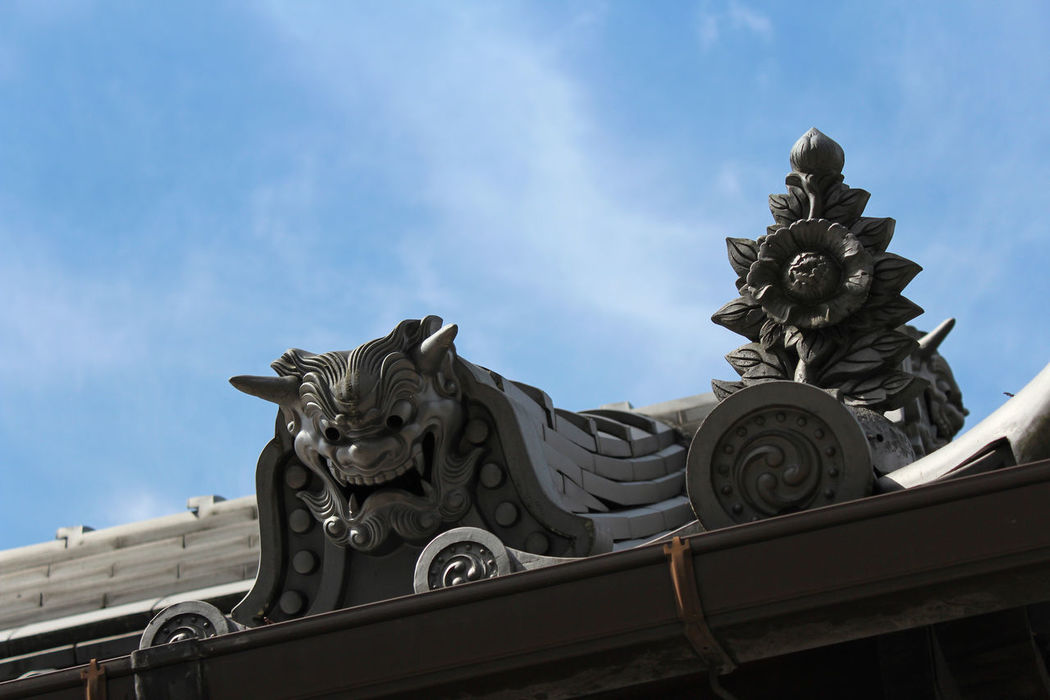 Antique Japanese ceramic roof tile decorated with swirling comma pattern called kawara and onigawara (鬼瓦) with the blue sky Architecture Building Exterior Built Structure Cloud - Sky Day Decorations Gargoyle History Low Angle View No People Outdoors Roof Sculpture Sky Statue Travel Destinations 鬼瓦