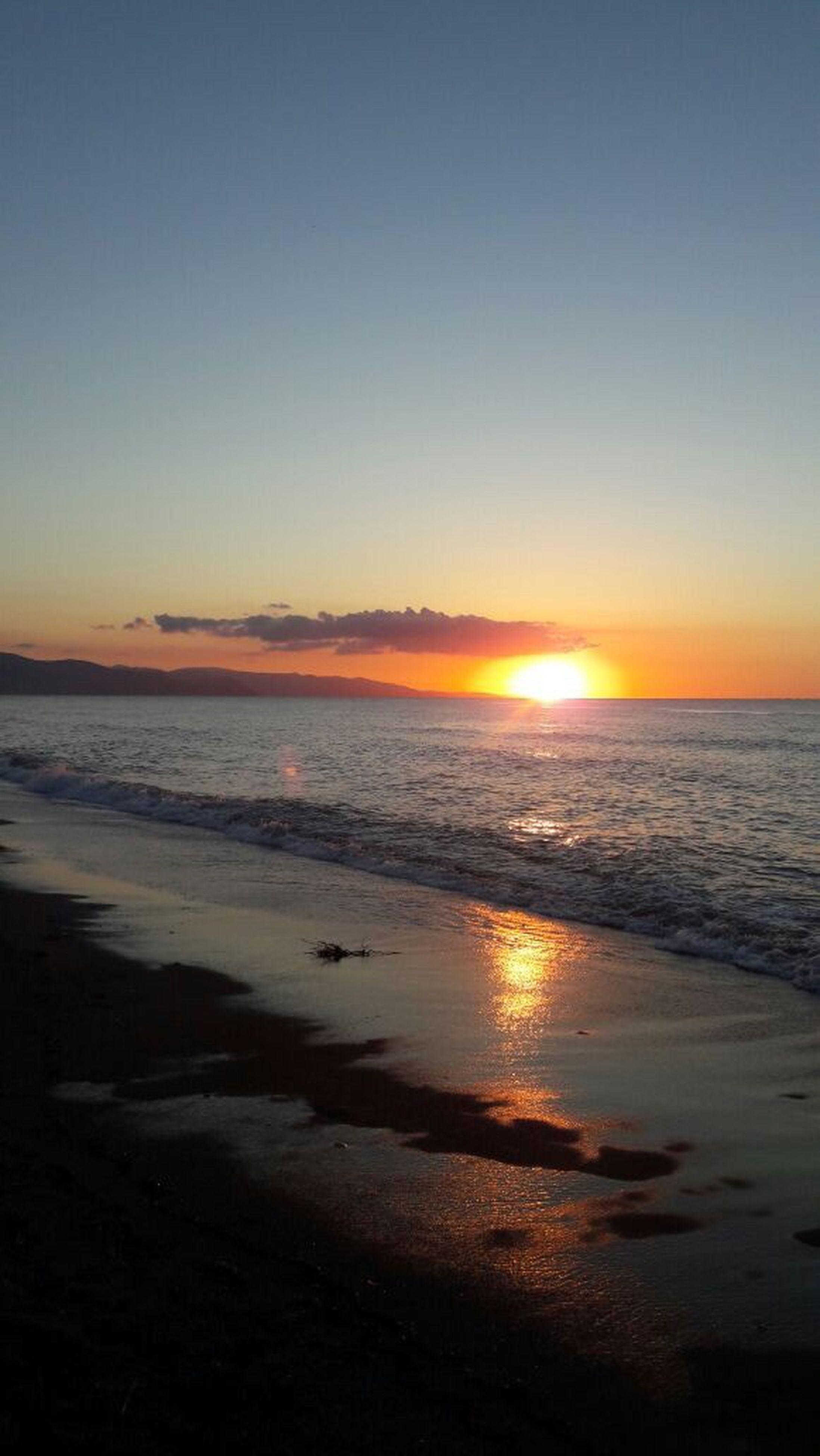 sunset, sea, water, beach, horizon over water, scenics, tranquil scene, shore, beauty in nature, tranquility, sun, orange color, sky, idyllic, nature, wave, coastline, outdoors, remote, calm, no people, non-urban scene, seascape, ocean, majestic, tourism