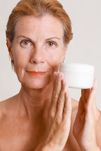 Attractive middle-aged woman with bare shoulders smiling and holding a jar of face cream alongside her face, close up studio portrait, Bare Care Wellness Aging Anti Applying Attractive Cosmetics Cream Facial Grooming Healthy Jar Middle Middle Aged Moisturizer Old Pampering Product Promoting Skin Skincare Toiletry Treatment Women