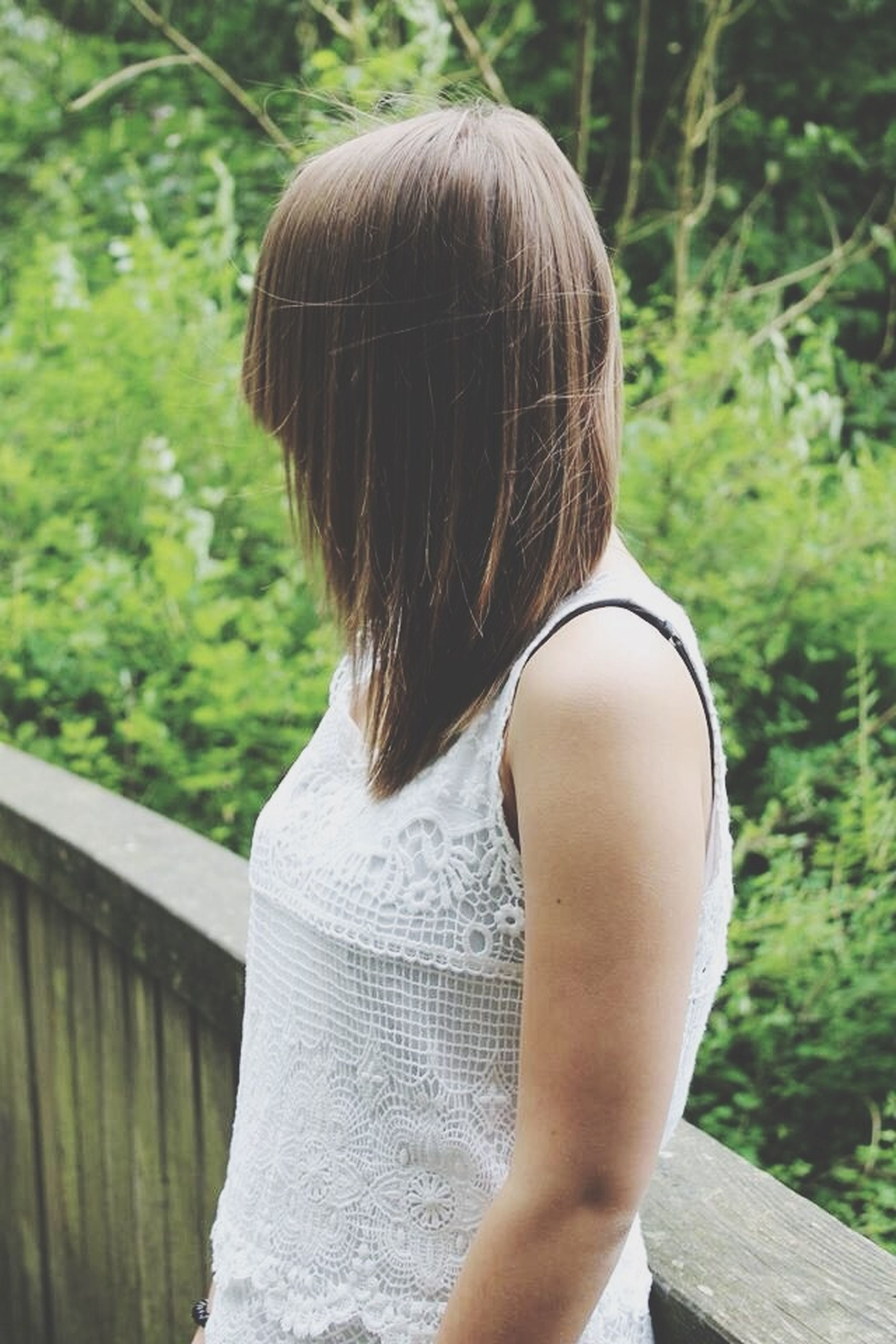 lifestyles, focus on foreground, leisure activity, rear view, person, holding, casual clothing, waist up, long hair, close-up, standing, day, headshot, outdoors, tree, blond hair, brown hair