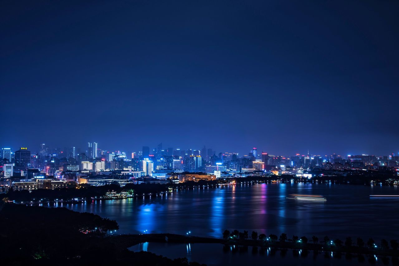 architecture, building exterior, city, cityscape, night, illuminated, skyscraper, built structure, river, water, travel destinations, no people, outdoors, blue, waterfront, modern, urban skyline, sky, nature