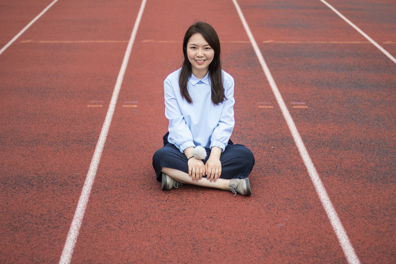 Beautiful Woman Black Hair Cross-legged Crouching Day Exercising Front View Full Length Happiness Kneeling Leisure Activity Lifestyles Looking At Camera One Person Outdoors Portrait Real People Running Track Sitting Smiling Sport Sports Track Track And Field Young Adult Young Women
