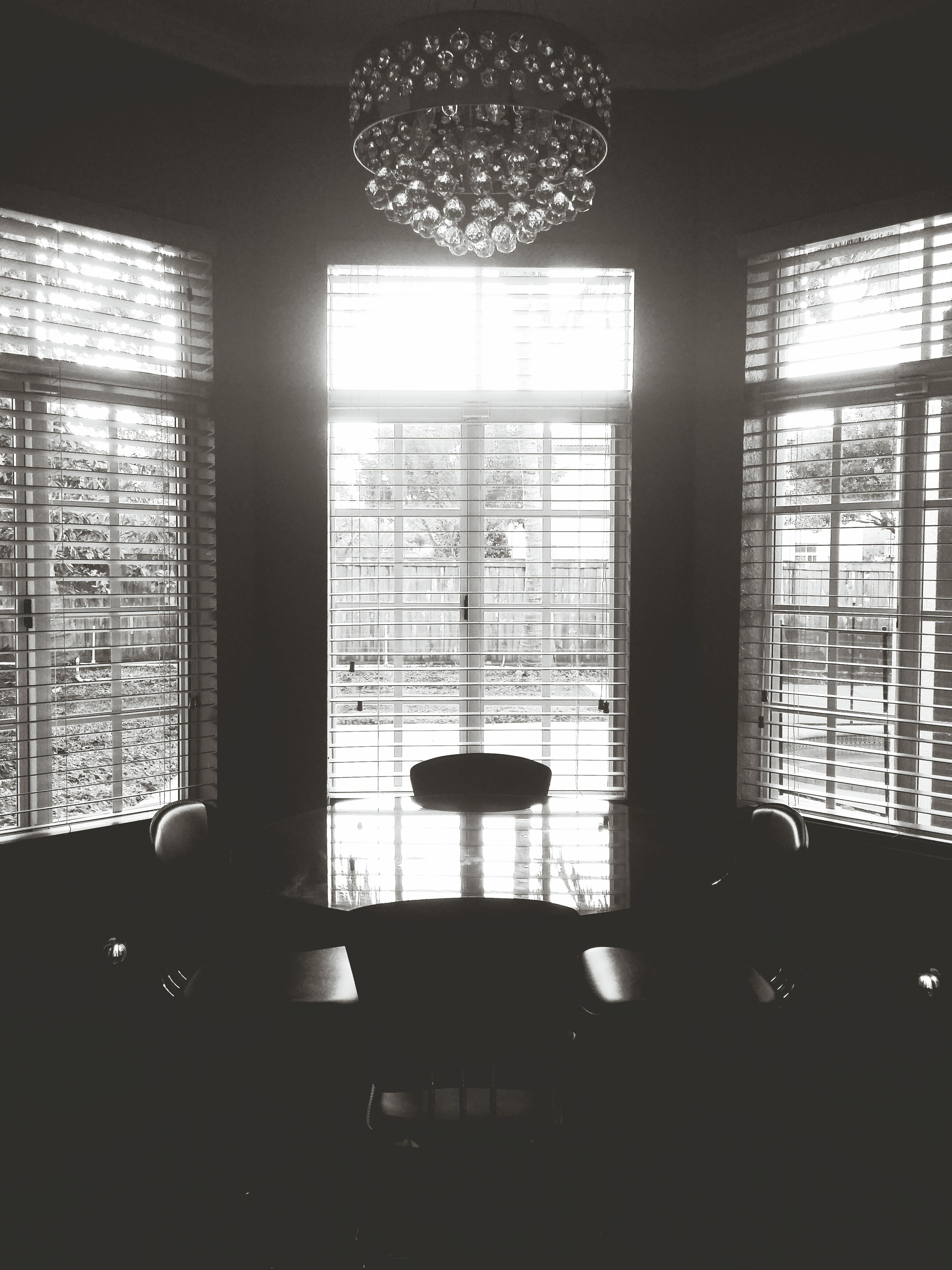 indoors, window, glass - material, home interior, lighting equipment, transparent, electric lamp, empty, ceiling, absence, chair, table, interior, architecture, illuminated, built structure, domestic room, hanging, chandelier, room