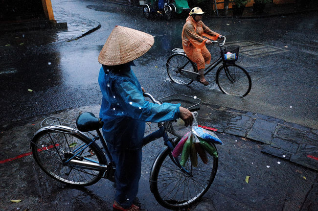 a rainy day in Hoi An town Bicycle Bicycle Basket Bicycles Cycle Day Hoian, Vietnam Land Vehicle Mode Of Transport Non La Outdoors Parked Parking Parking Lot Rain Rain Coat Rainy Days Road Stationary Street Street Vendor Transportation Travel Photography