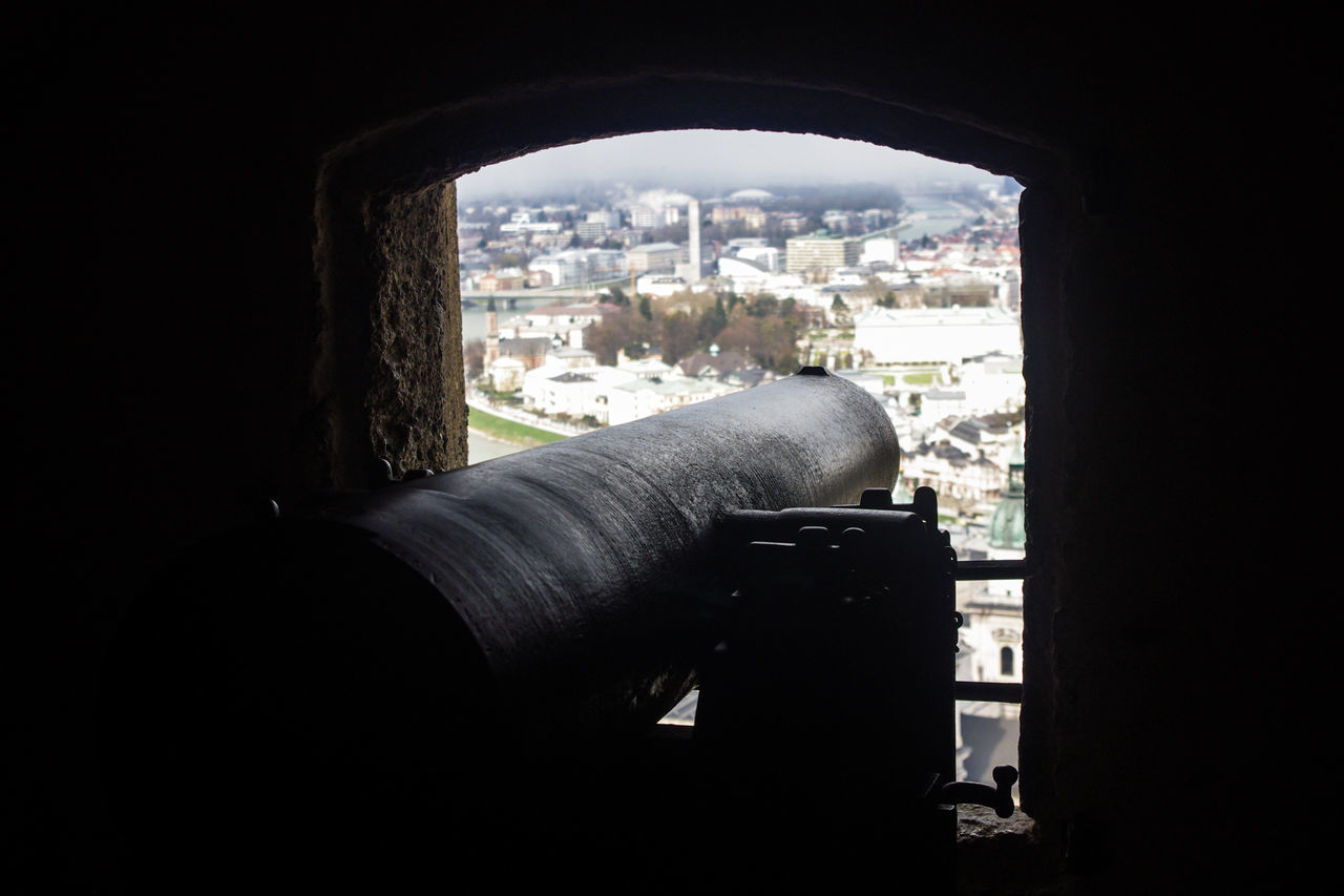 architecture, weapon, window, built structure, indoors, cannon, history, building exterior, day, no people, cityscape, canon, city, sky
