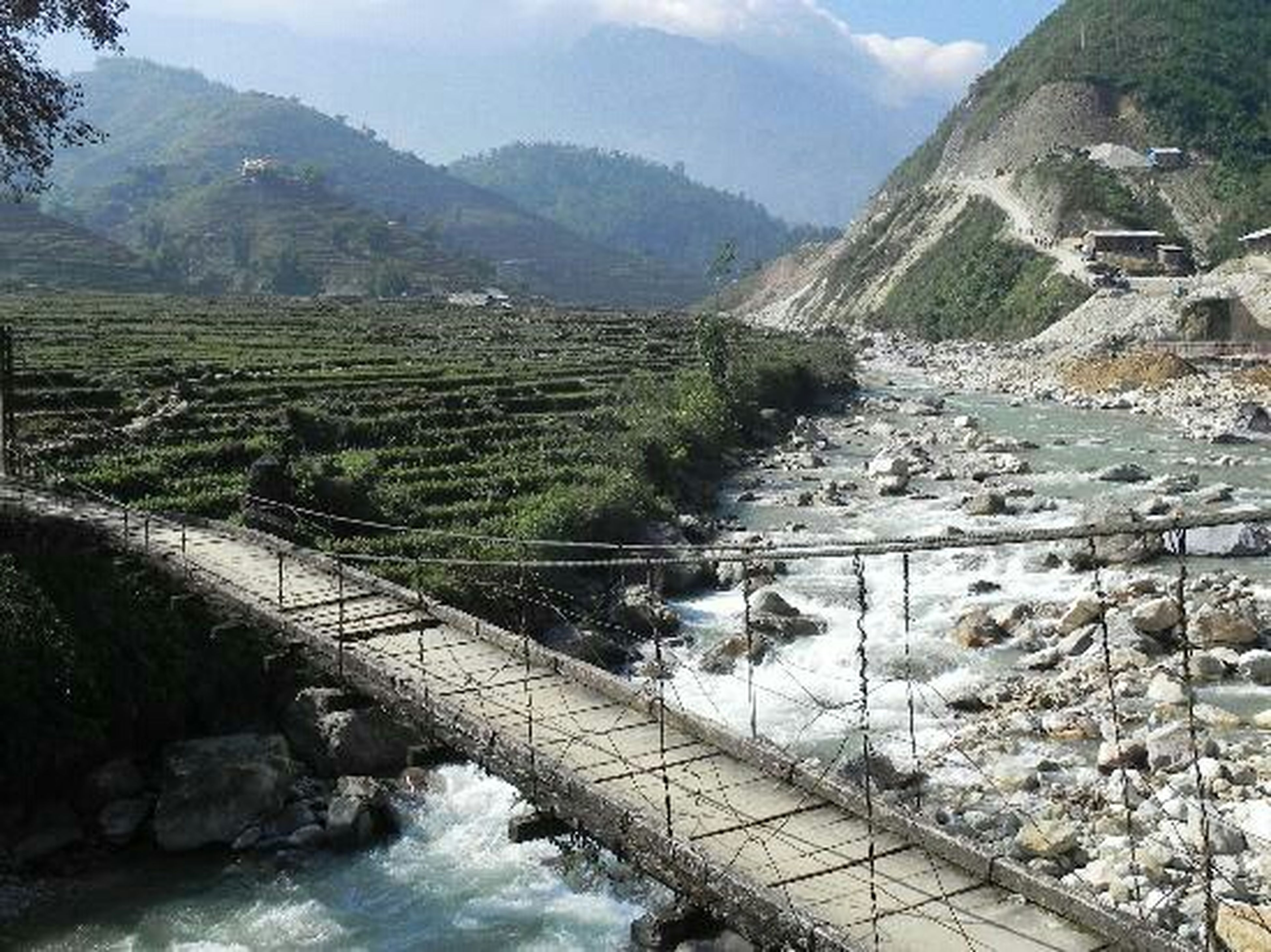 mountain, water, river, built structure, mountain range, scenics, tranquility, rock - object, high angle view, beauty in nature, tranquil scene, nature, architecture, sky, landscape, flowing water, railing, bridge - man made structure, connection, day