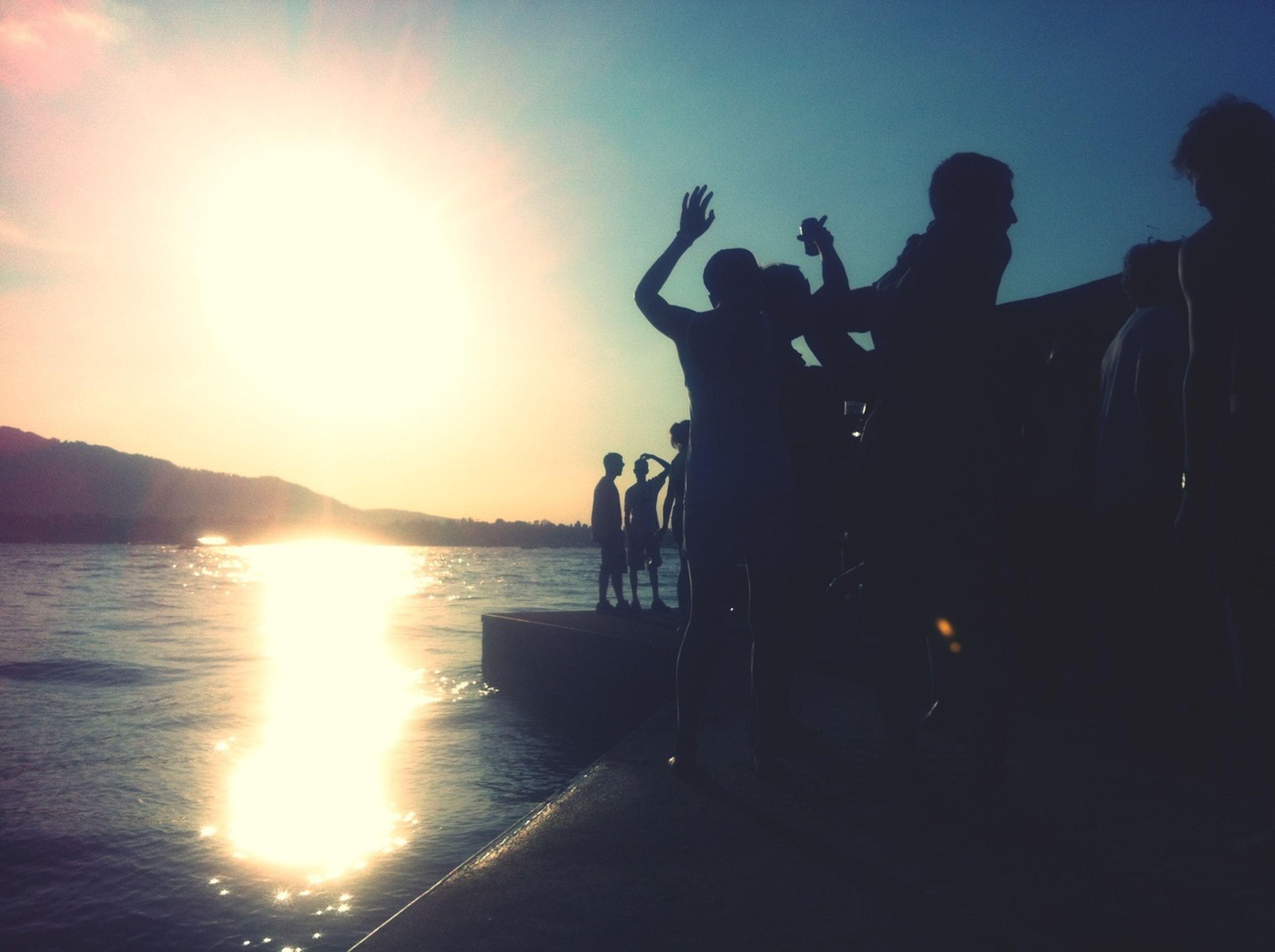 sun, water, sunset, sunlight, sunbeam, silhouette, sea, lifestyles, lens flare, leisure activity, sky, men, beach, medium group of people, person, shore, nature, travel, sunny