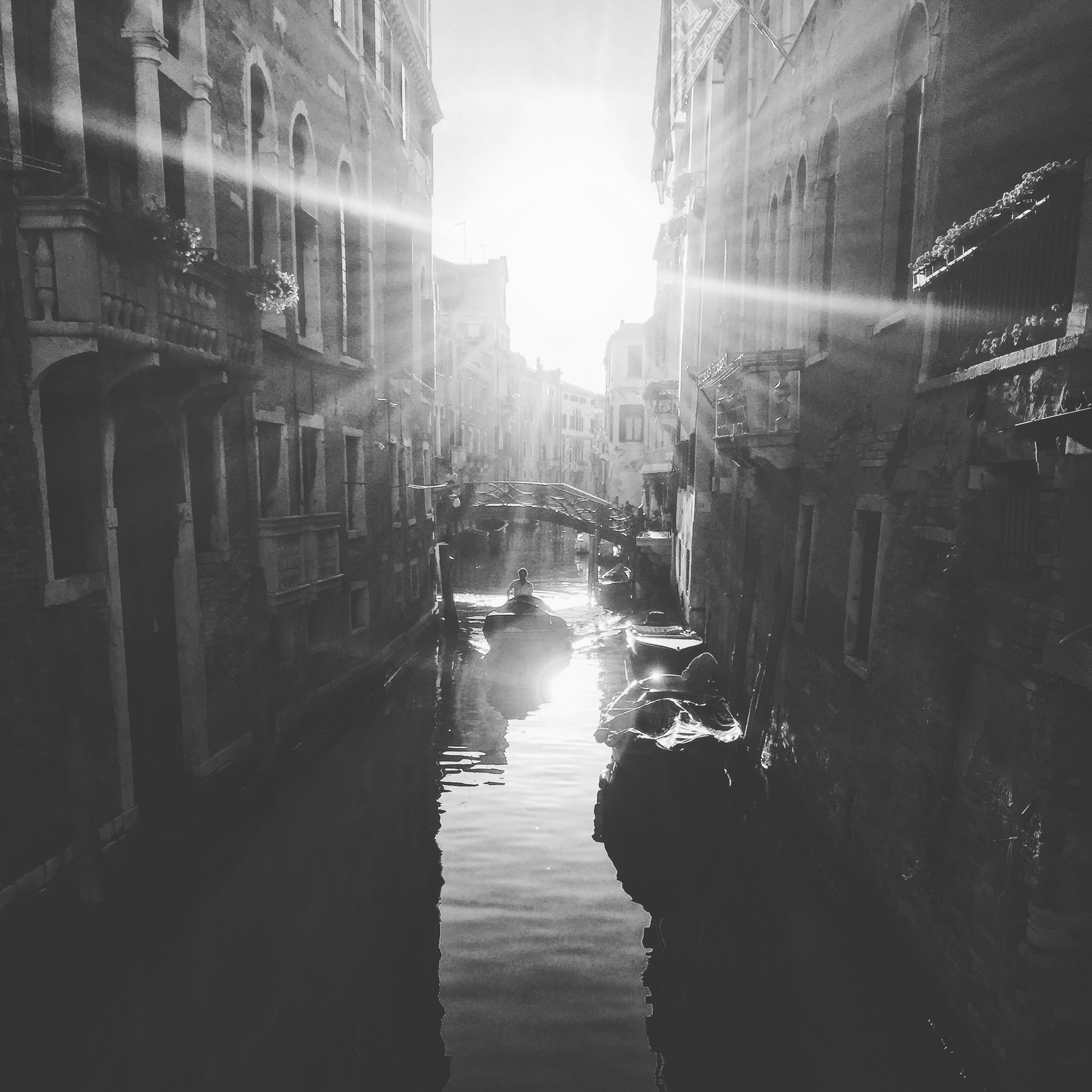 architecture, building exterior, built structure, water, canal, city, reflection, building, waterfront, sunlight, transportation, residential building, sun, incidental people, mode of transport, residential structure, street, wet, lens flare, sky