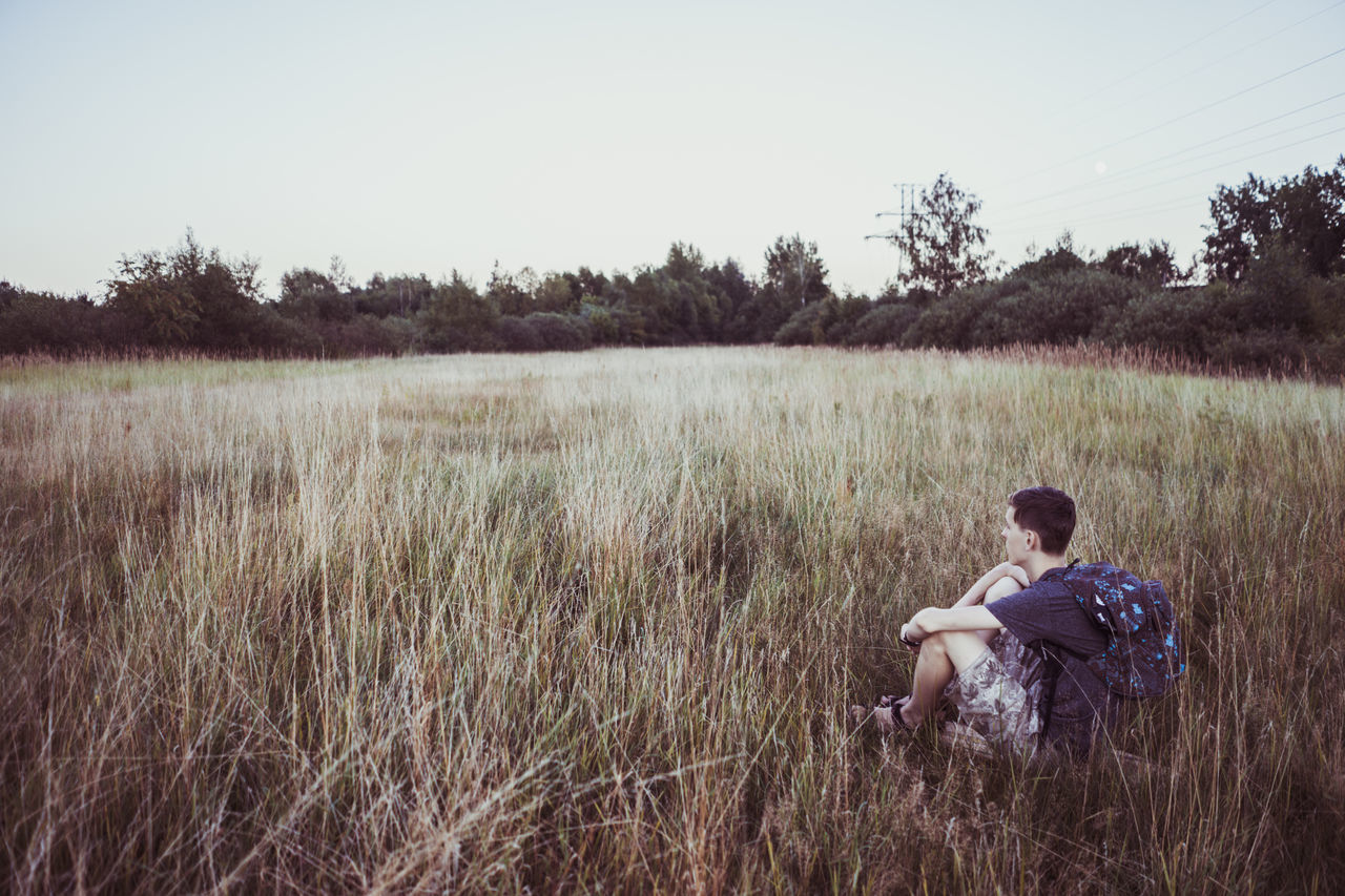 one person, grass, full length, field, outdoors, tree, childhood, nature, landscape, sitting, clear sky, day, sky, people, adult