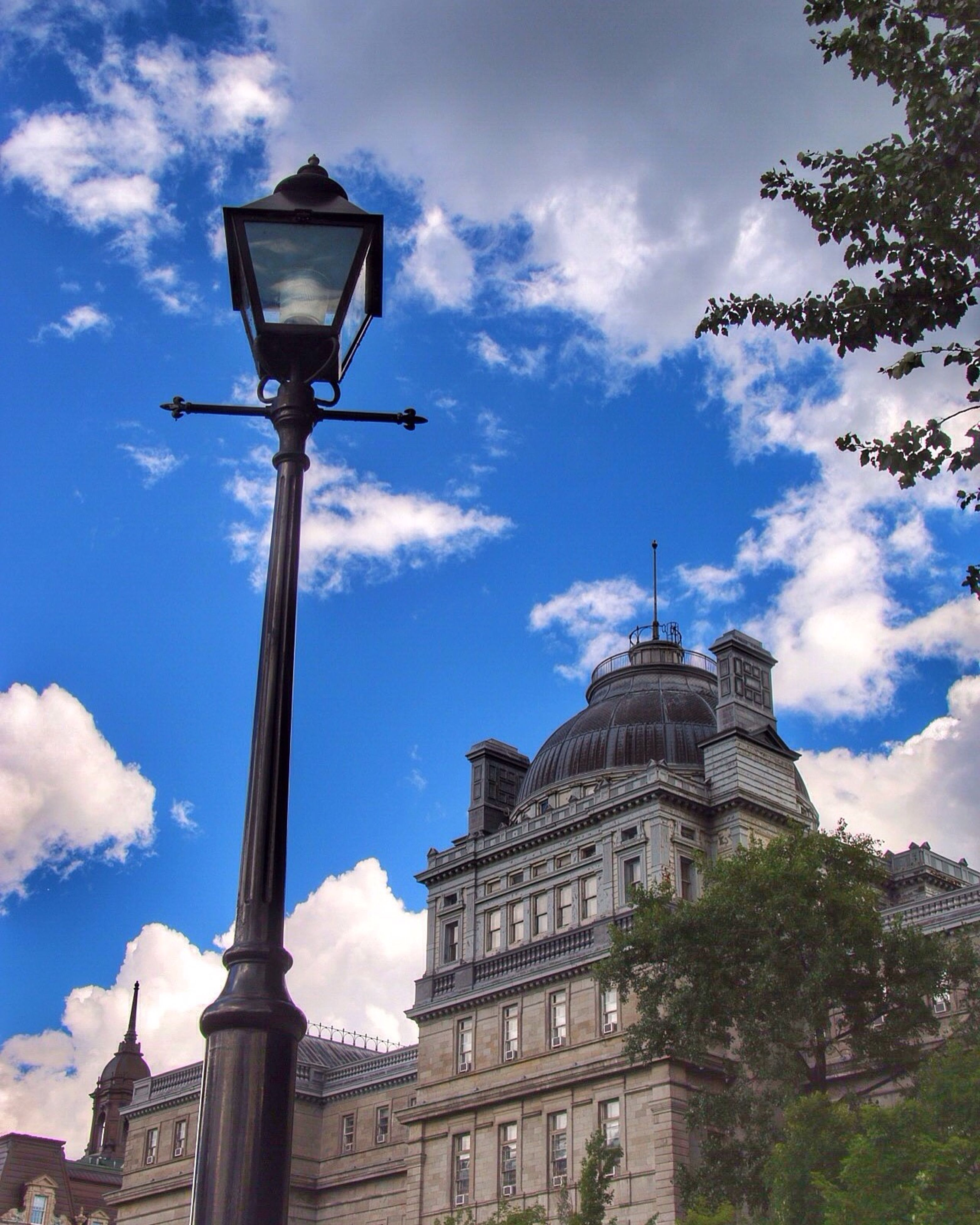 street light, architecture, low angle view, built structure, lighting equipment, building exterior, travel destinations, tourism, sky, famous place, blue, travel, city, lamp post, cloud, outdoors, international landmark, tall - high, history, cloud - sky, day, capital cities, high section, no people, architectural feature, place of worship