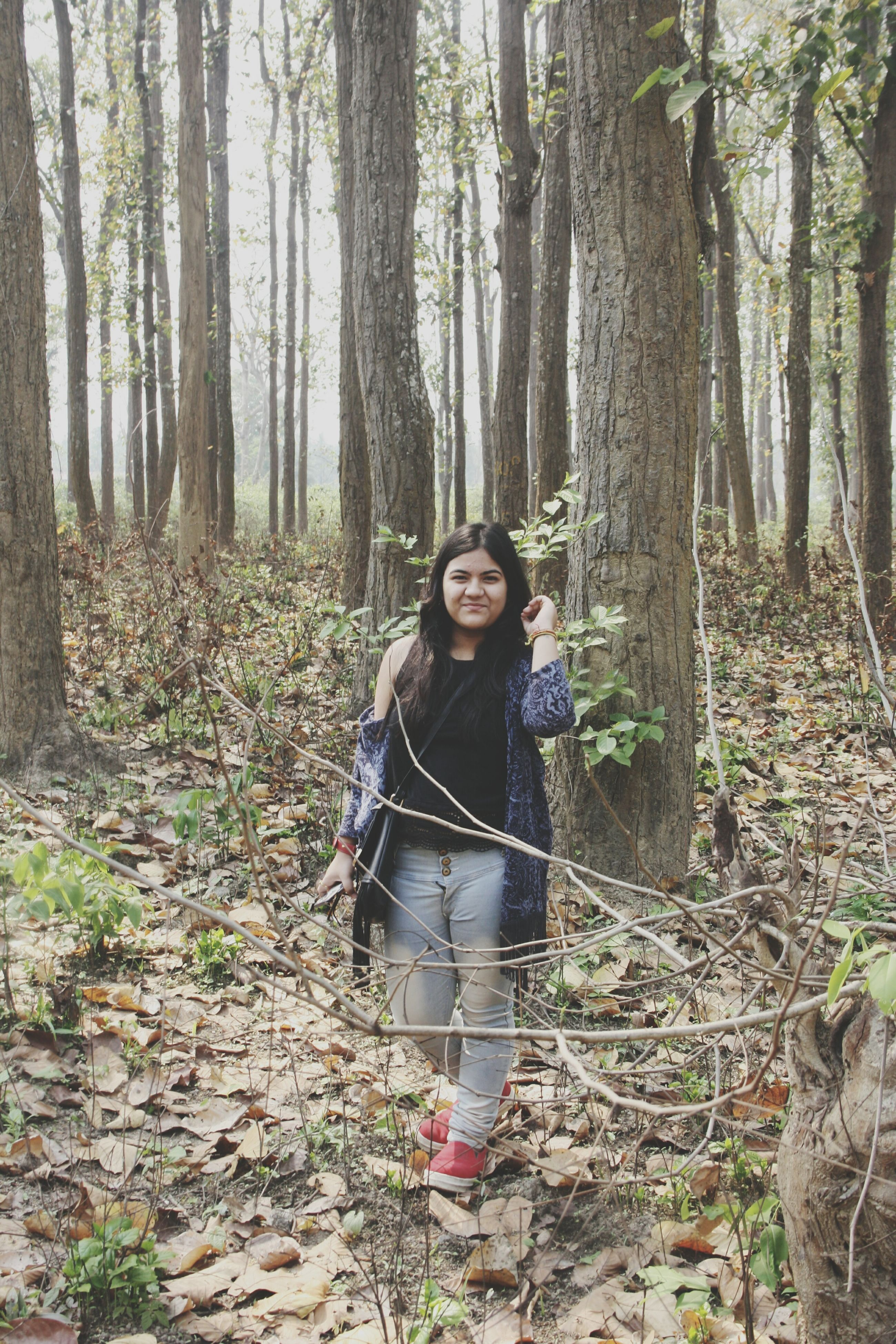 forest, tree, tree trunk, one person, standing, nature, woodland, day, smiling, outdoors, leisure activity, full length, growth, lifestyles, looking at camera, portrait, real people, branch, beauty in nature, young adult, people, adults only, adult