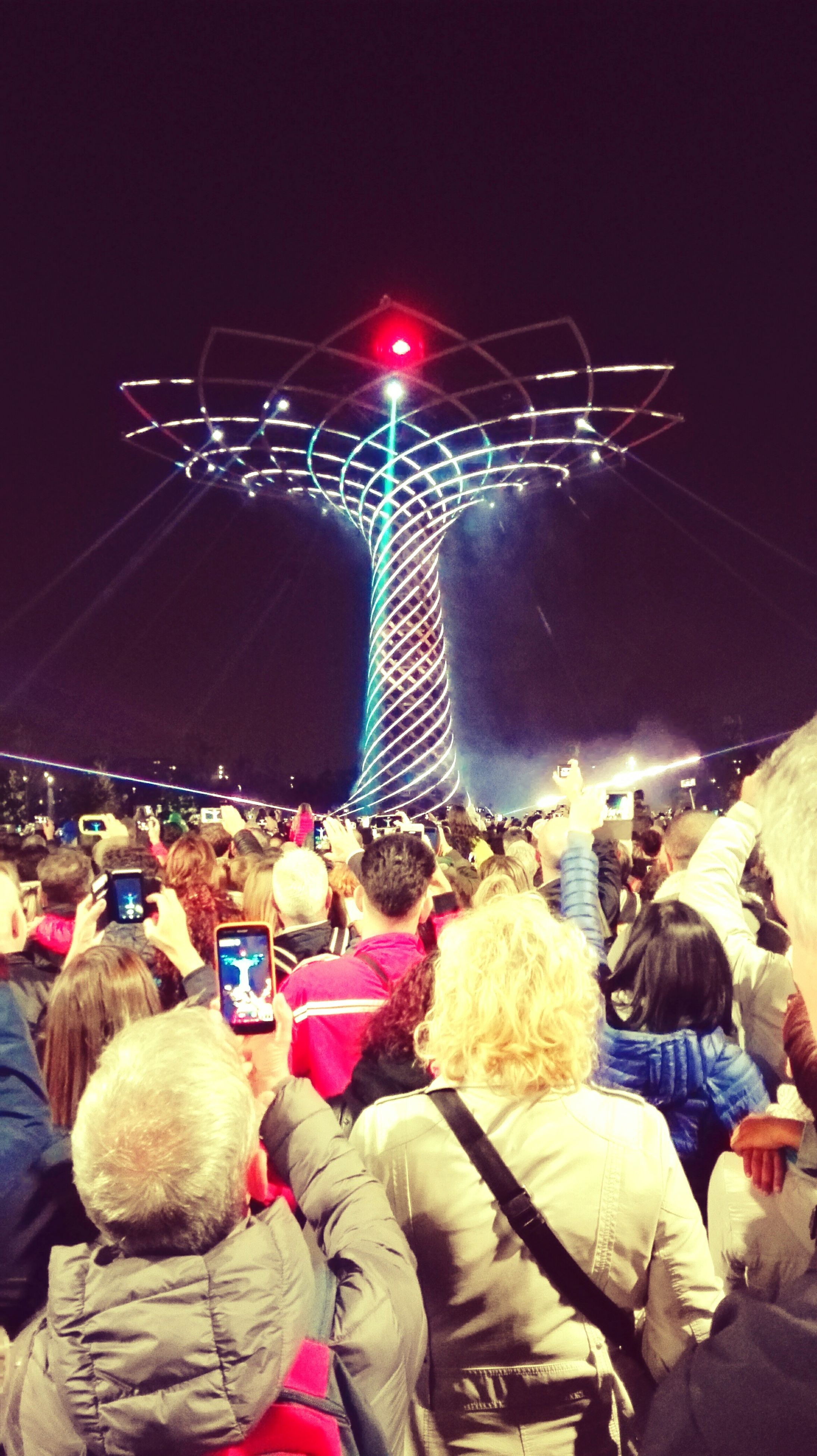 night, lifestyles, leisure activity, men, arts culture and entertainment, illuminated, person, music, performance, celebration, large group of people, enjoyment, event, togetherness, fun, rear view, standing, holding