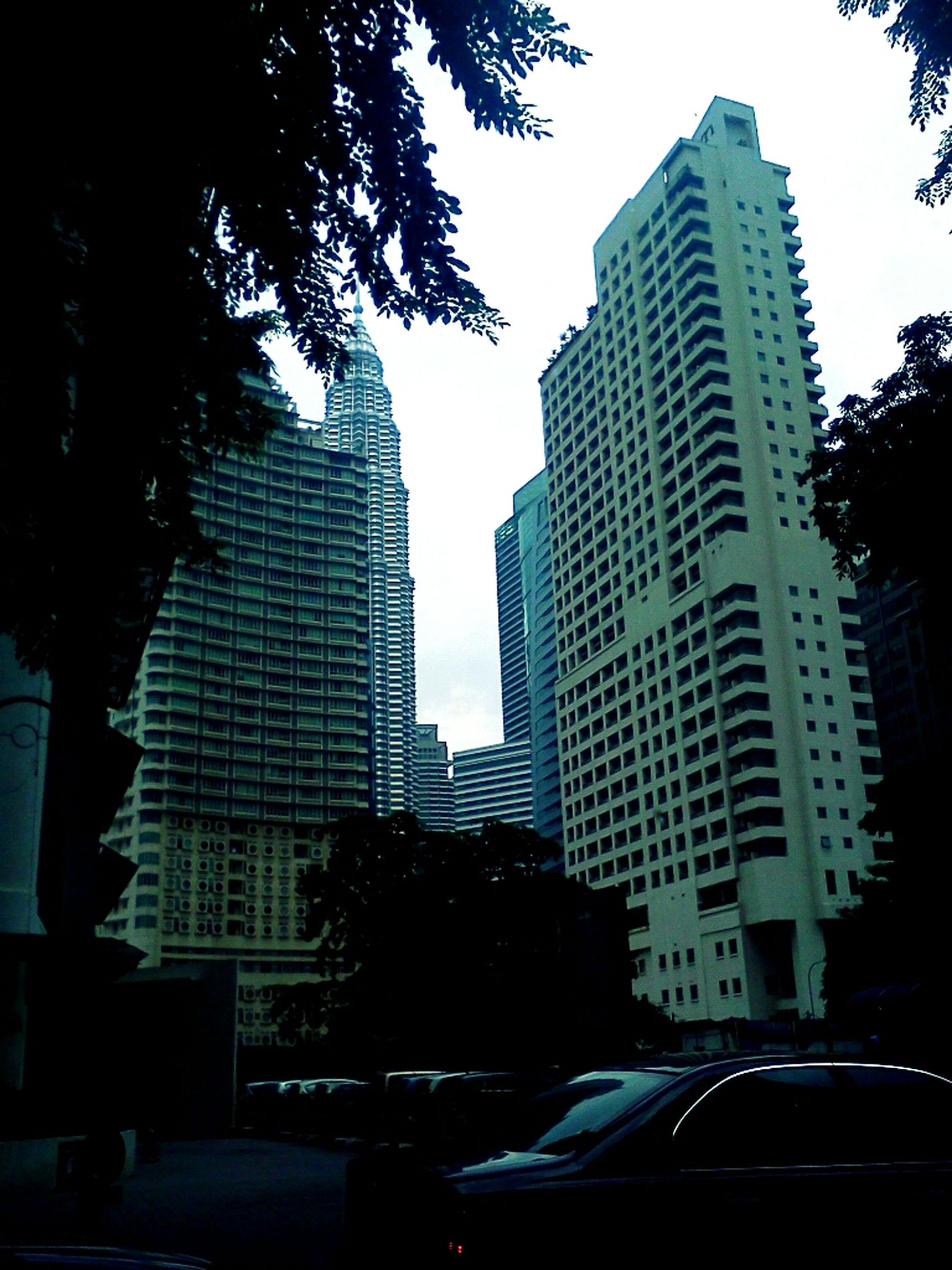 building exterior, architecture, city, skyscraper, built structure, tall - high, car, office building, transportation, modern, land vehicle, street, tower, tree, clear sky, building, city life, mode of transport, road, tall