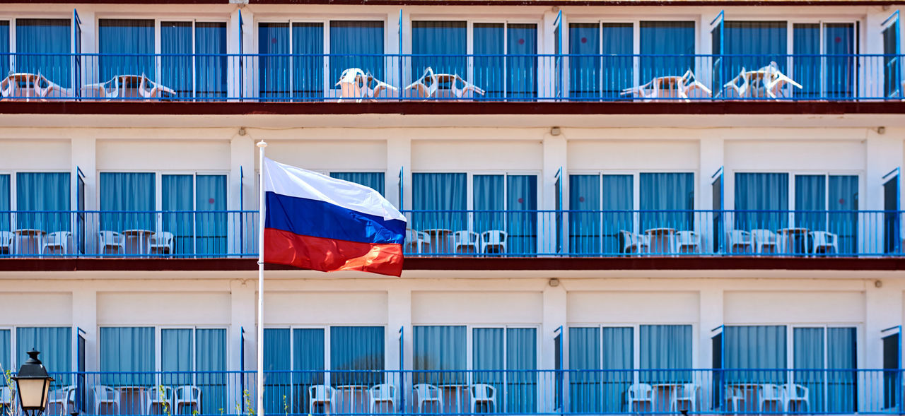 Flag of Russia against hotel balconies Accommodations Apartments Architecture Balcony Blue Building Exterior Day Exterior Facade Building Flag Greeting Holiday Hotel National Flag No People Nobody Outdoors Resort Russia Summer Symbol Tourism Travel Vacations Windows