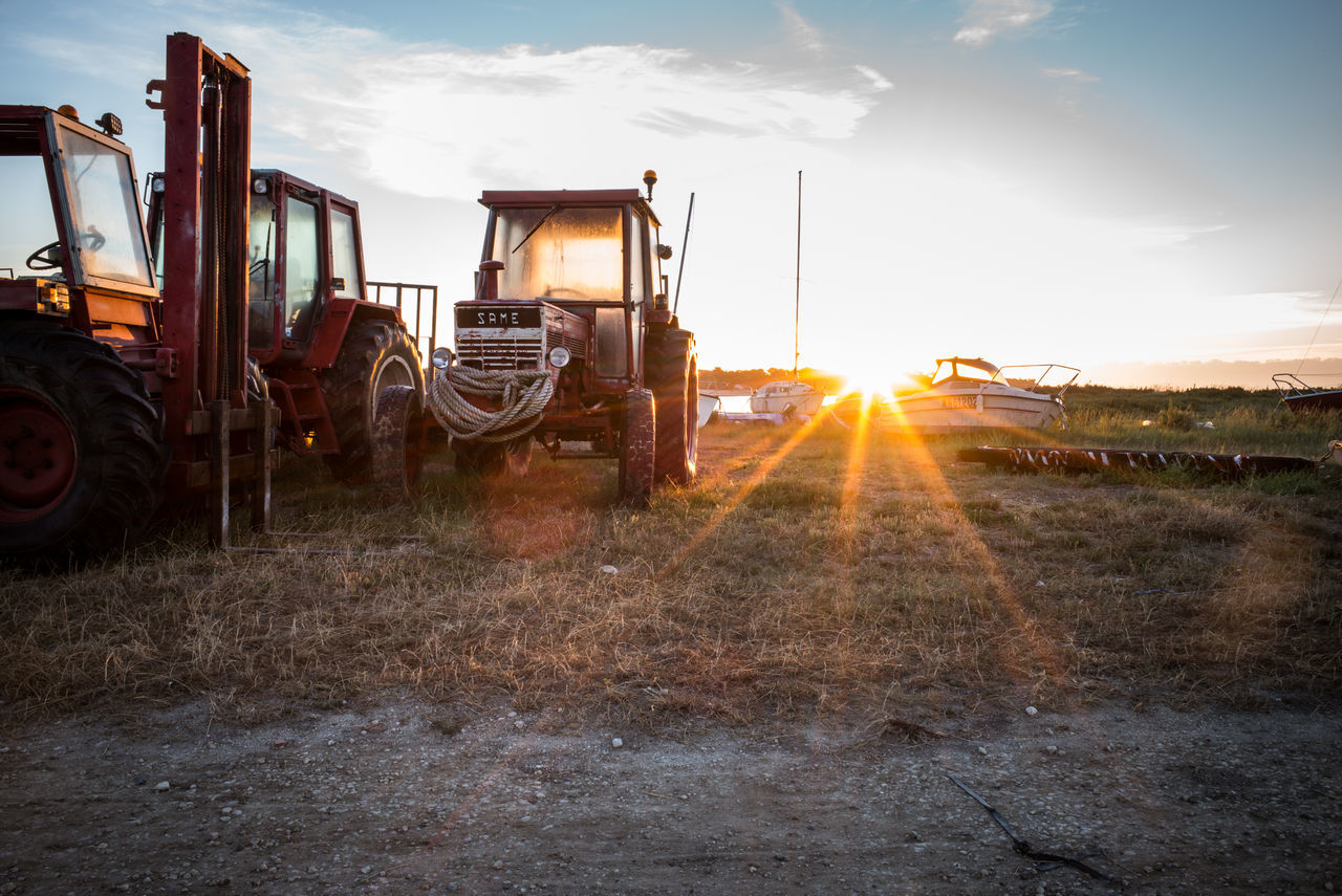 sky, lens flare, transportation, field, cloud - sky, land vehicle, sunlight, agricultural machinery, mode of transport, sun, no people, construction machinery, grass, outdoors, sunset, industry, nature, day