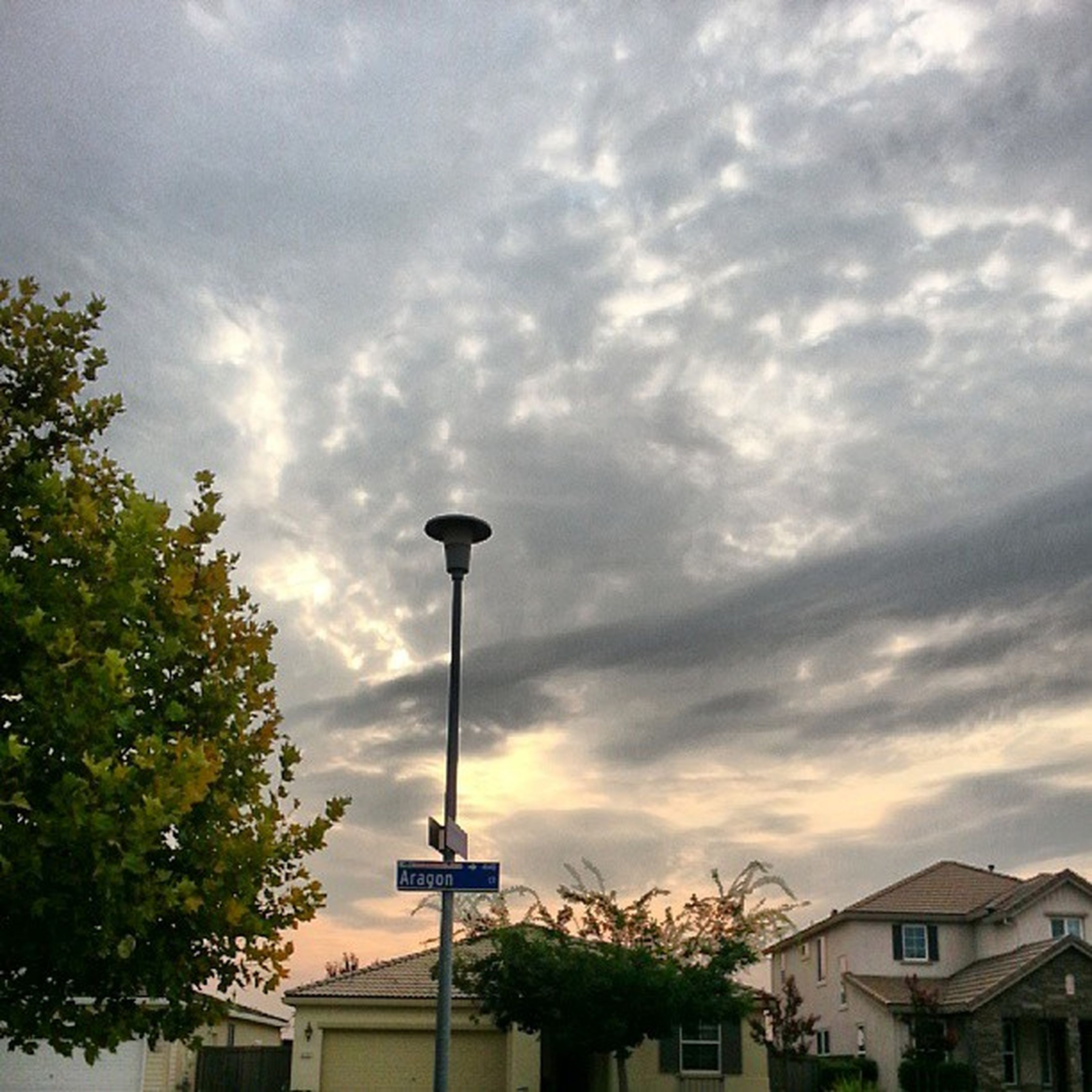 sky, building exterior, cloud - sky, architecture, built structure, cloudy, street light, tree, low angle view, cloud, weather, overcast, house, residential building, residential structure, city, outdoors, storm cloud, nature, day