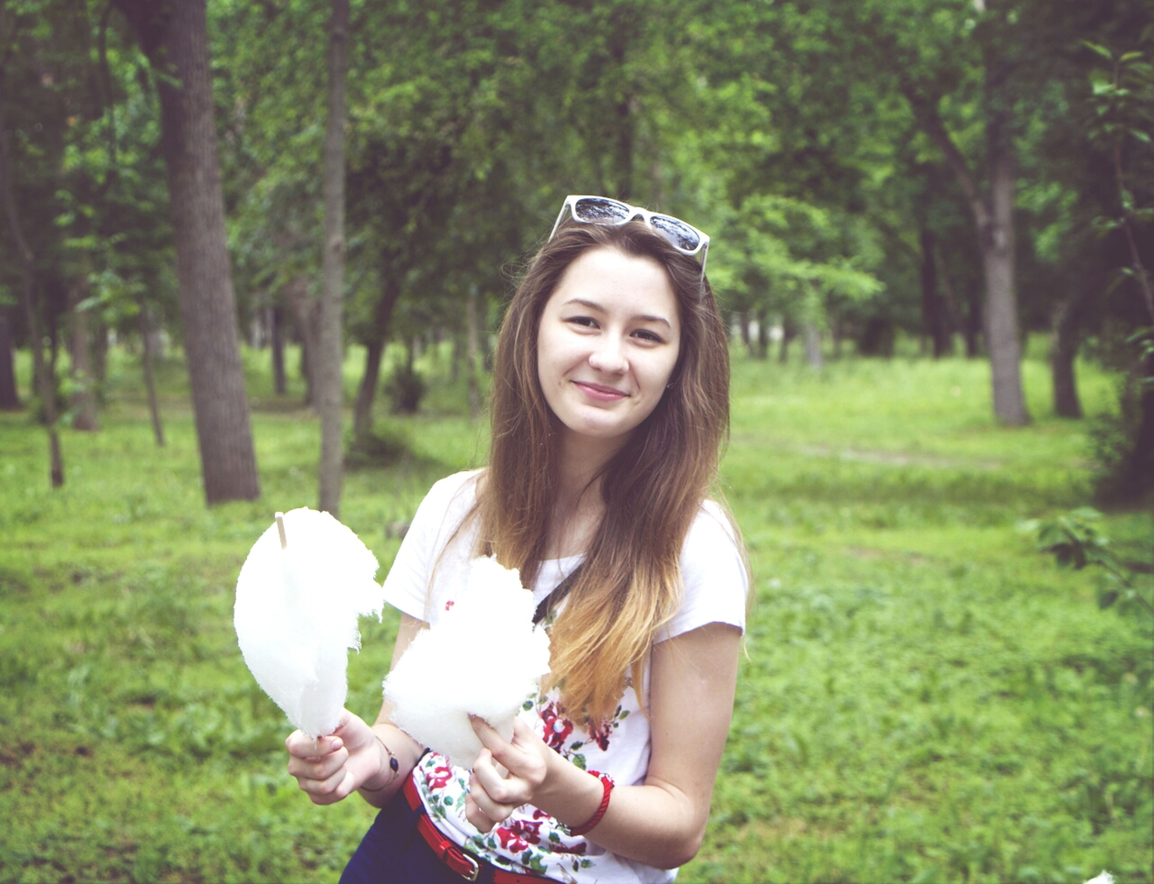 person, young adult, young women, lifestyles, leisure activity, focus on foreground, portrait, looking at camera, front view, flower, tree, smiling, long hair, casual clothing, happiness, standing, park - man made space