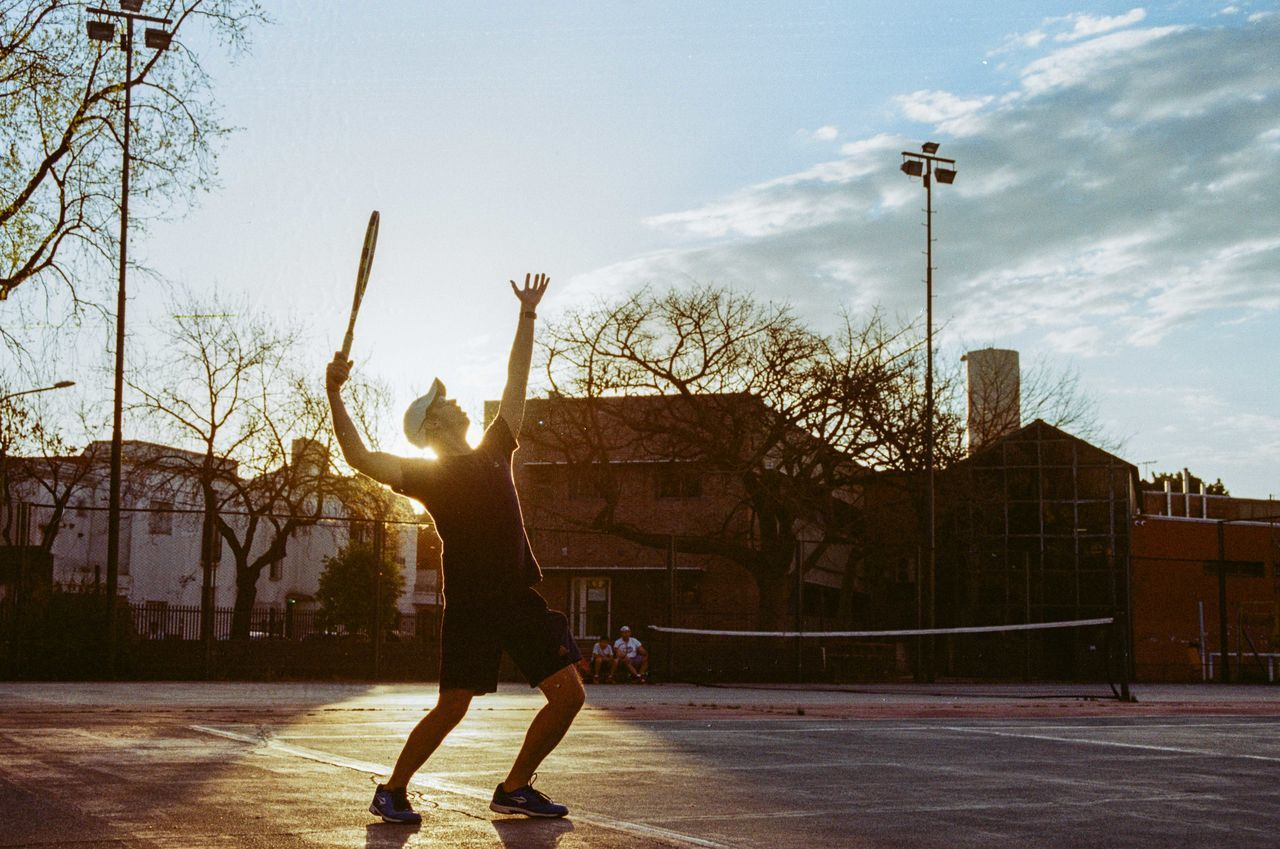 real people, built structure, architecture, building exterior, sky, lifestyles, tree, leisure activity, bare tree, men, outdoors, skill, day, one person, basketball - sport, city, full length, cloud - sky, court, basketball hoop, handstand, skateboard park, only men, people