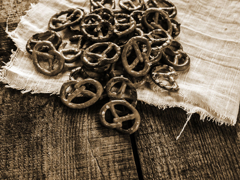 Heap of fresh Wheat salt pretzels on hessian linen fabric cloth and wooden table Circle Cloth Creativity Day Fabric Fresh Heap Hessian History Linen Pretzels Salt Surface Level Table Wheat Wooden