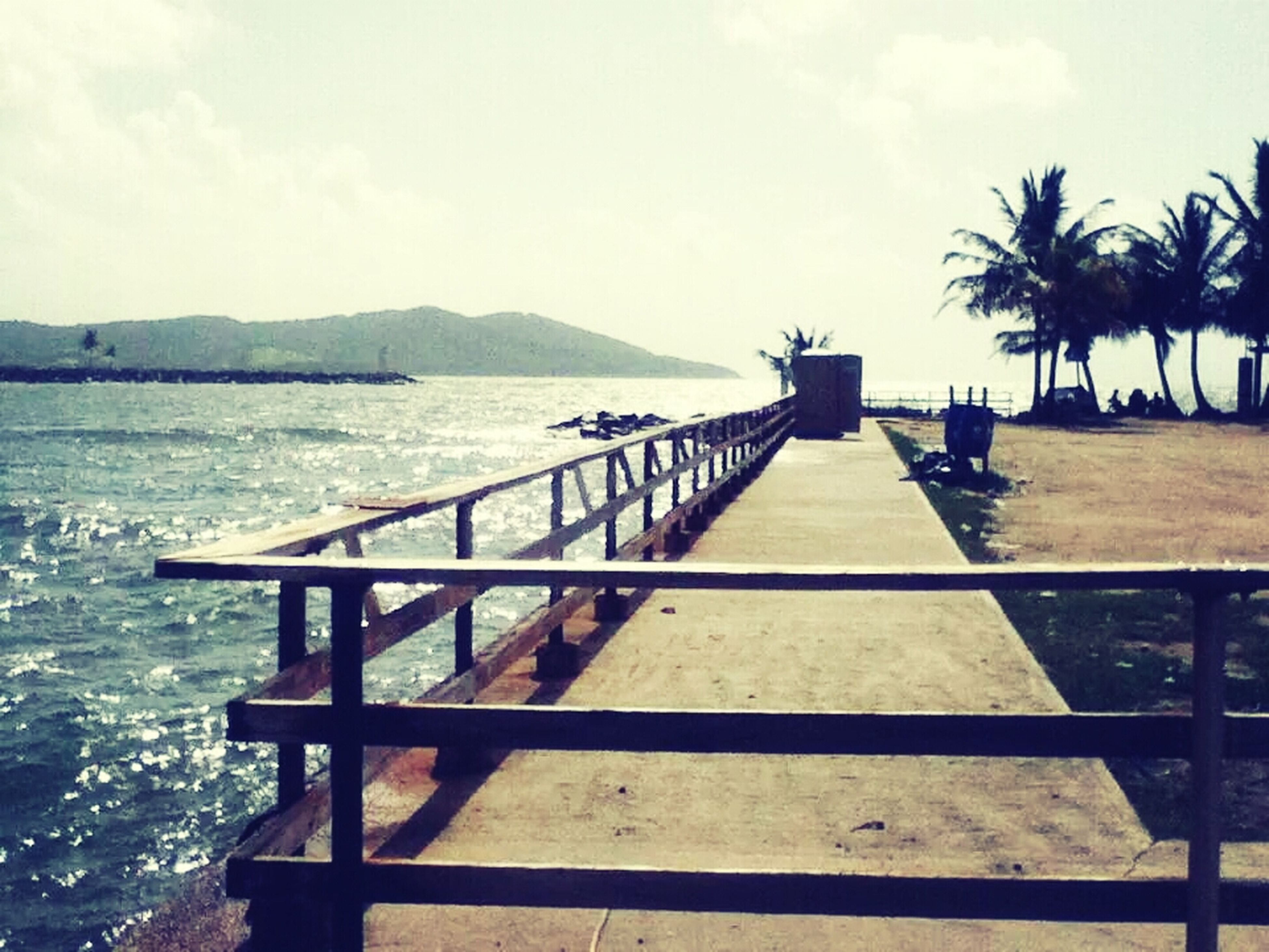 water, sea, railing, pier, sky, tranquil scene, tranquility, mountain, scenics, nature, beauty in nature, wood - material, jetty, built structure, horizon over water, the way forward, idyllic, outdoors, lake, boardwalk