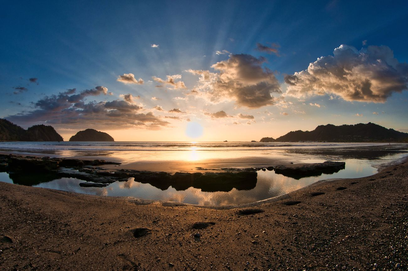 Playa Herradura, Costa Rica Sea Beach Water Reflection Beauty In Nature Horizon Over Water Scenics Nature Blue Sand Sky Sunlight Sunset Tranquility Idyllic Tranquil Scene Outdoors Sunbeam Cloud - Sky No People