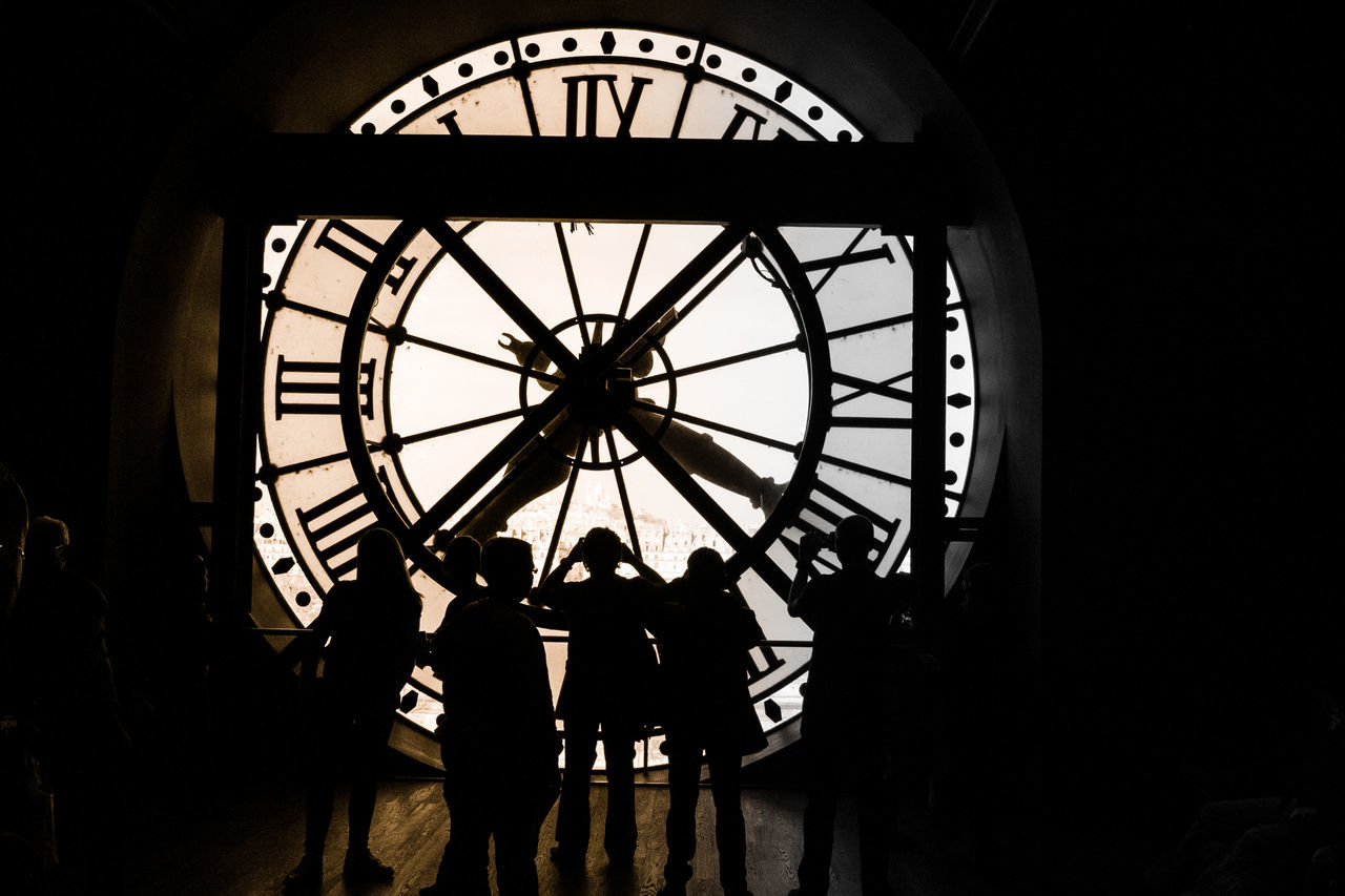 clock, silhouette, time, indoors, real people, roman numeral, built structure, architecture, day, men, travel destinations, clock face, low angle view, minute hand, people