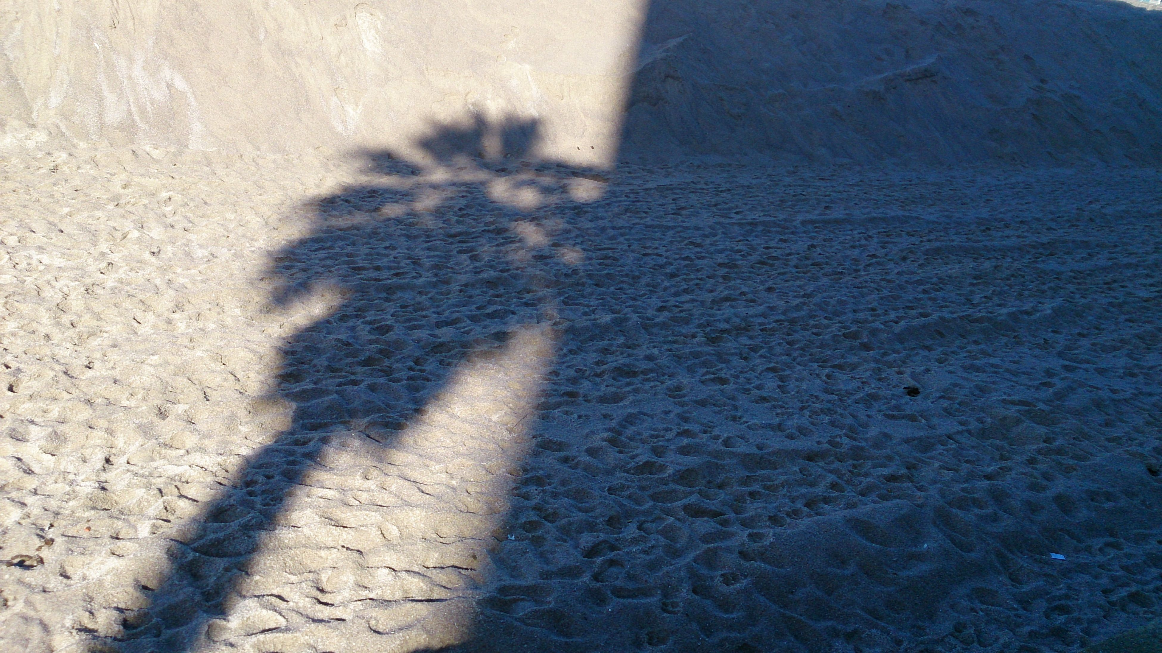 sand, shadow, beach, sunlight, focus on shadow, high angle view, shore, lifestyles, leisure activity, unrecognizable person, outdoors, day, footprint, nature, walking, standing, men, street