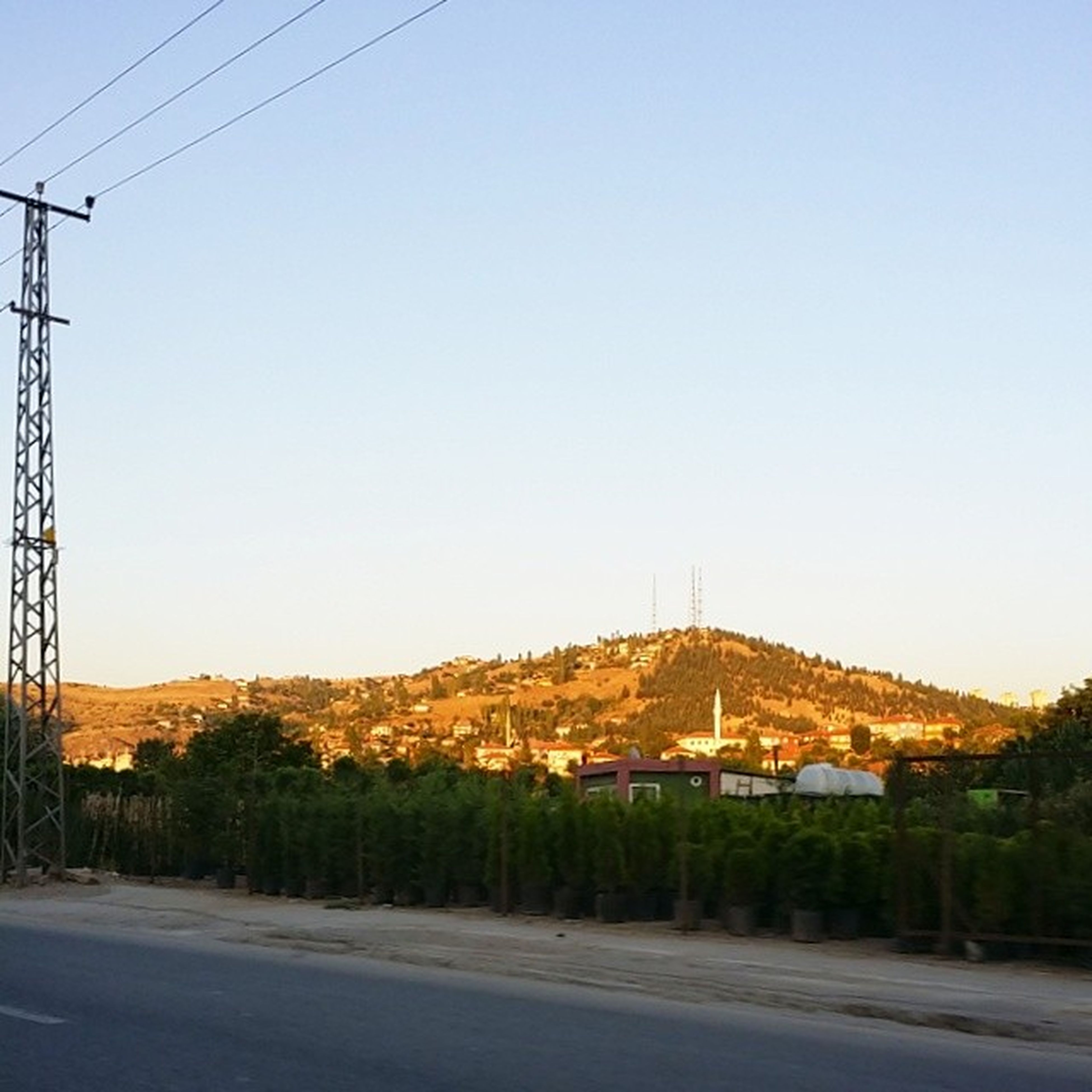 clear sky, power line, electricity pylon, building exterior, copy space, built structure, cable, architecture, road, electricity, power supply, house, transportation, blue, fuel and power generation, connection, street, the way forward, power cable, tree