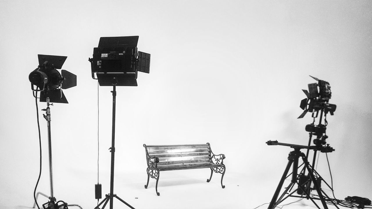 Studio lights and bench Photography Themes Tripod Arts Culture And Entertainment Photographing Camera - Photographic Equipment Indoors  No People Technology Film Industry White Background Filming Behind The Scenes Day
