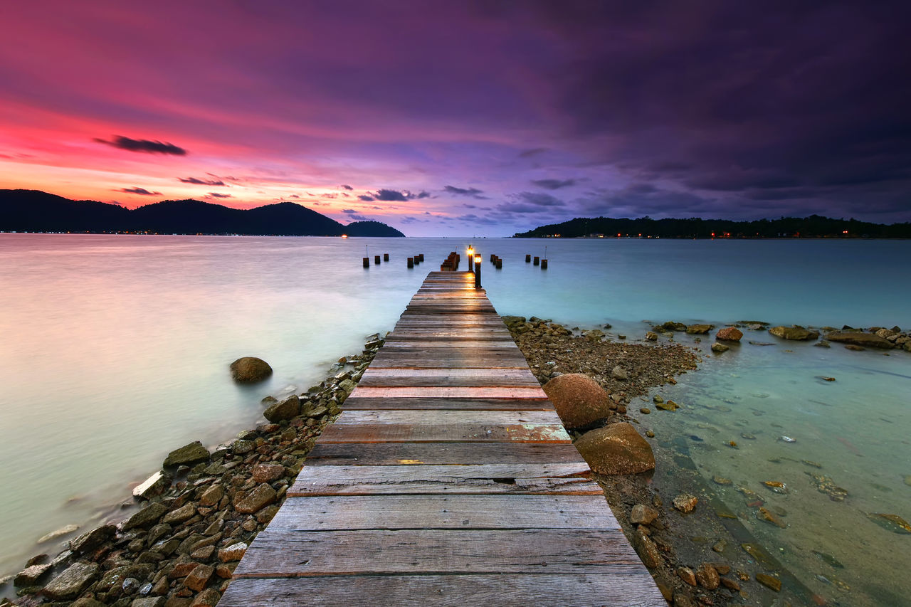 Wooden jetty at Marina Island, Lumut with beautiful sunset background. Beach Beauty In Nature Cloud - Sky Day EyeEm Best Shots EyeEm Gallery EyeEm Nature Lover Getty Images Getty X EyeEm Jetty Landscape Mountain Nature One Person Outdoors People Reflection Rock - Object Scenics Sea Sky Sunset Tranquil Scene Tranquility Water